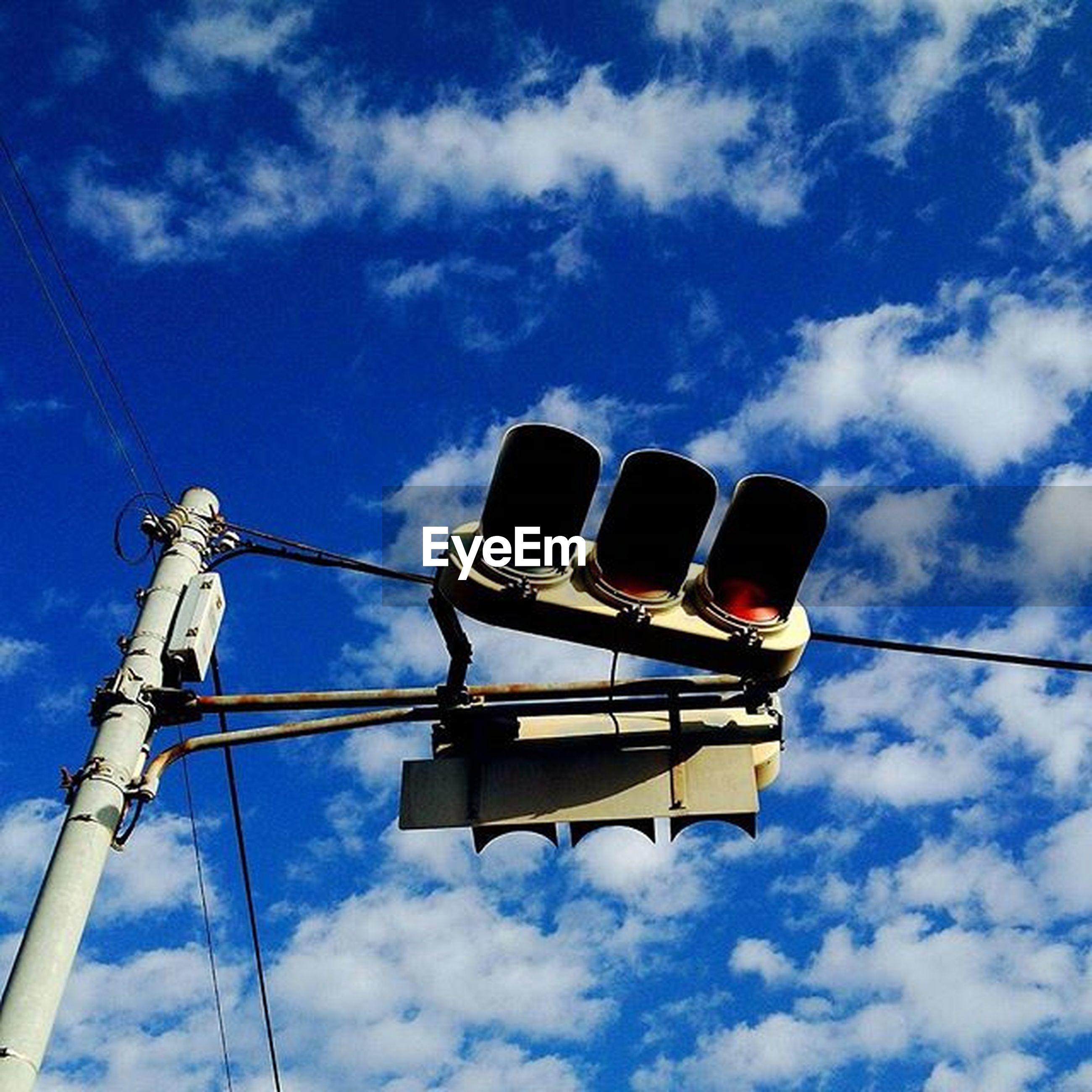 low angle view, sky, electricity, power line, cable, blue, technology, power supply, cloud - sky, fuel and power generation, cloud, lighting equipment, outdoors, no people, cloudy, connection, power cable, day, street light, electricity pylon