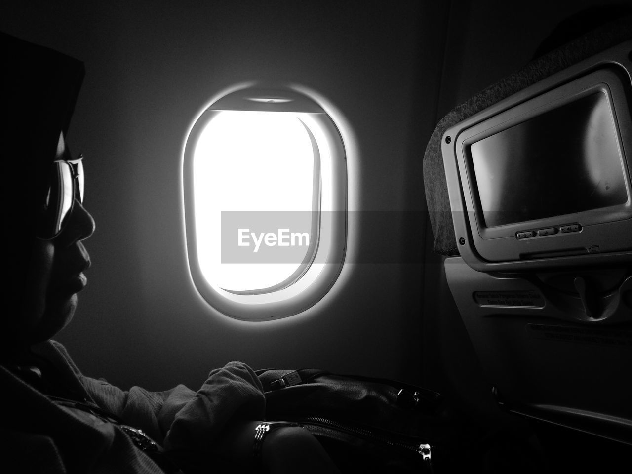 Man wearing sunglasses while sitting in airplane