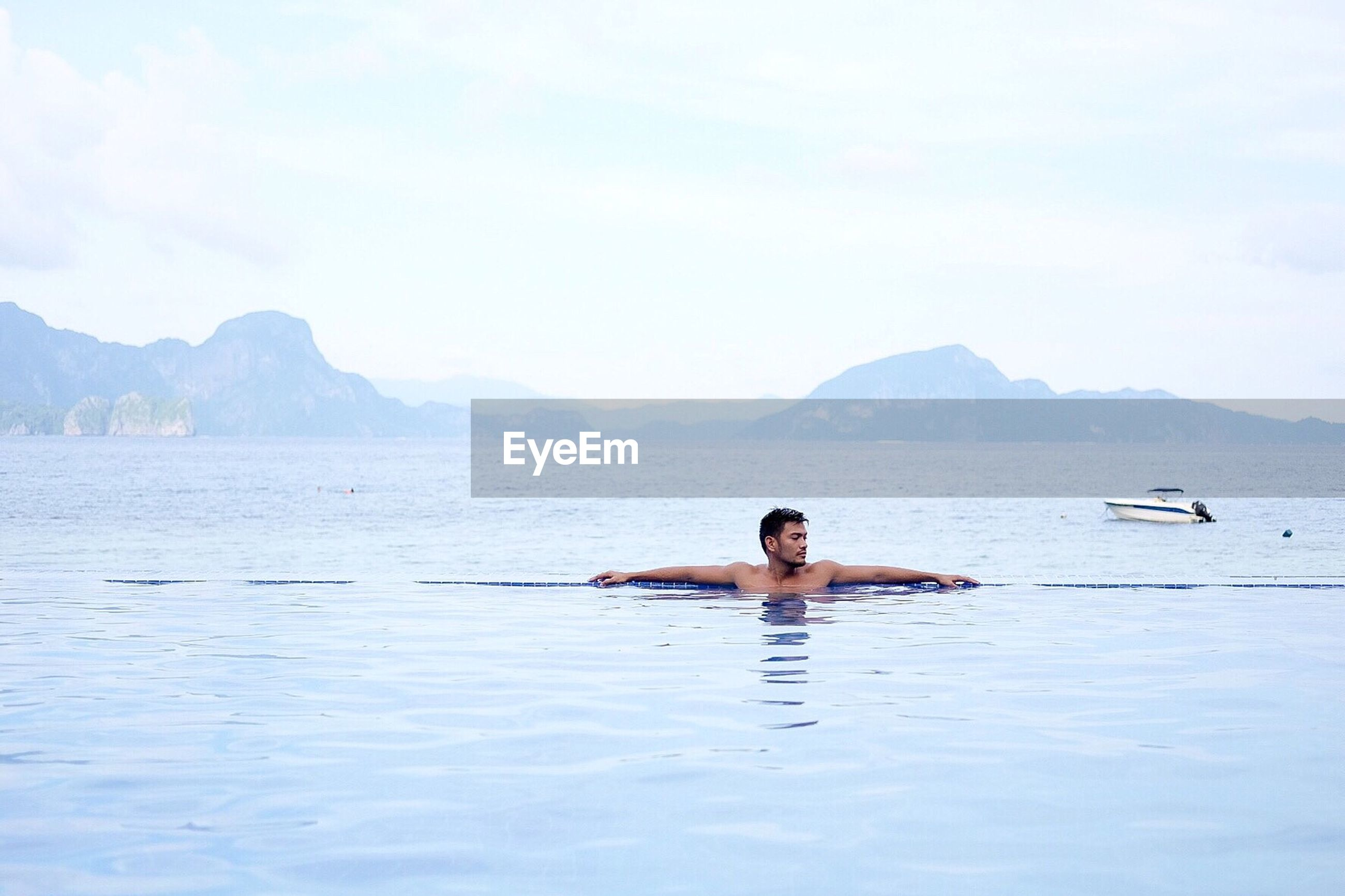 Man swimming in infinity pool by sea against sky