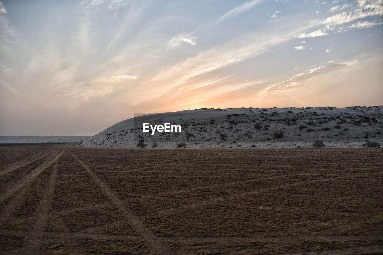 sky, scenics - nature, cloud - sky, beauty in nature, land, landscape, sunset, tranquil scene, environment, tranquility, nature, sand, non-urban scene, no people, outdoors, idyllic, remote, field, desert, climate, arid climate