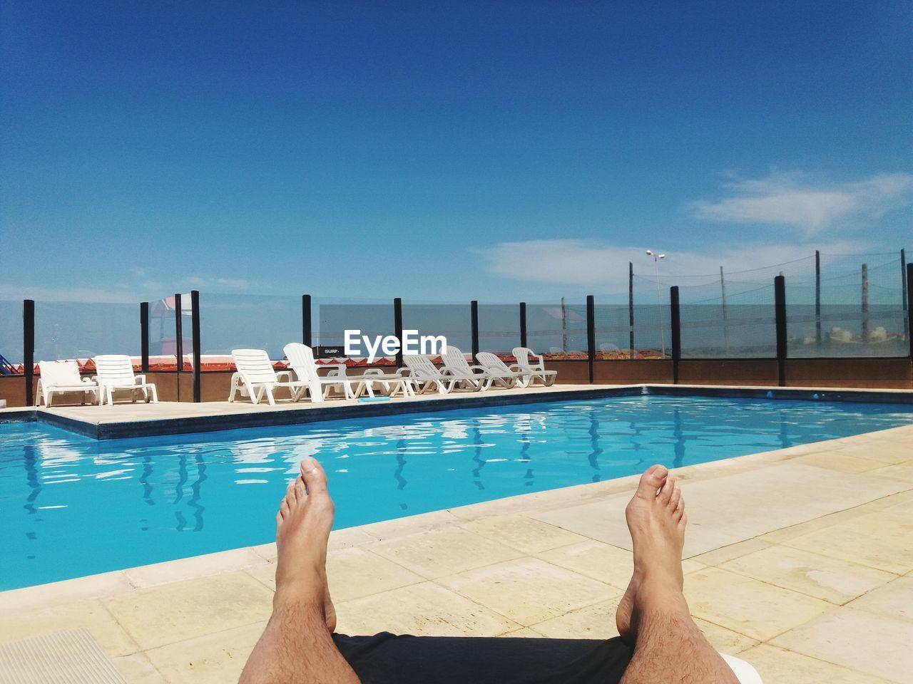relaxing in swimming pool against blue sky