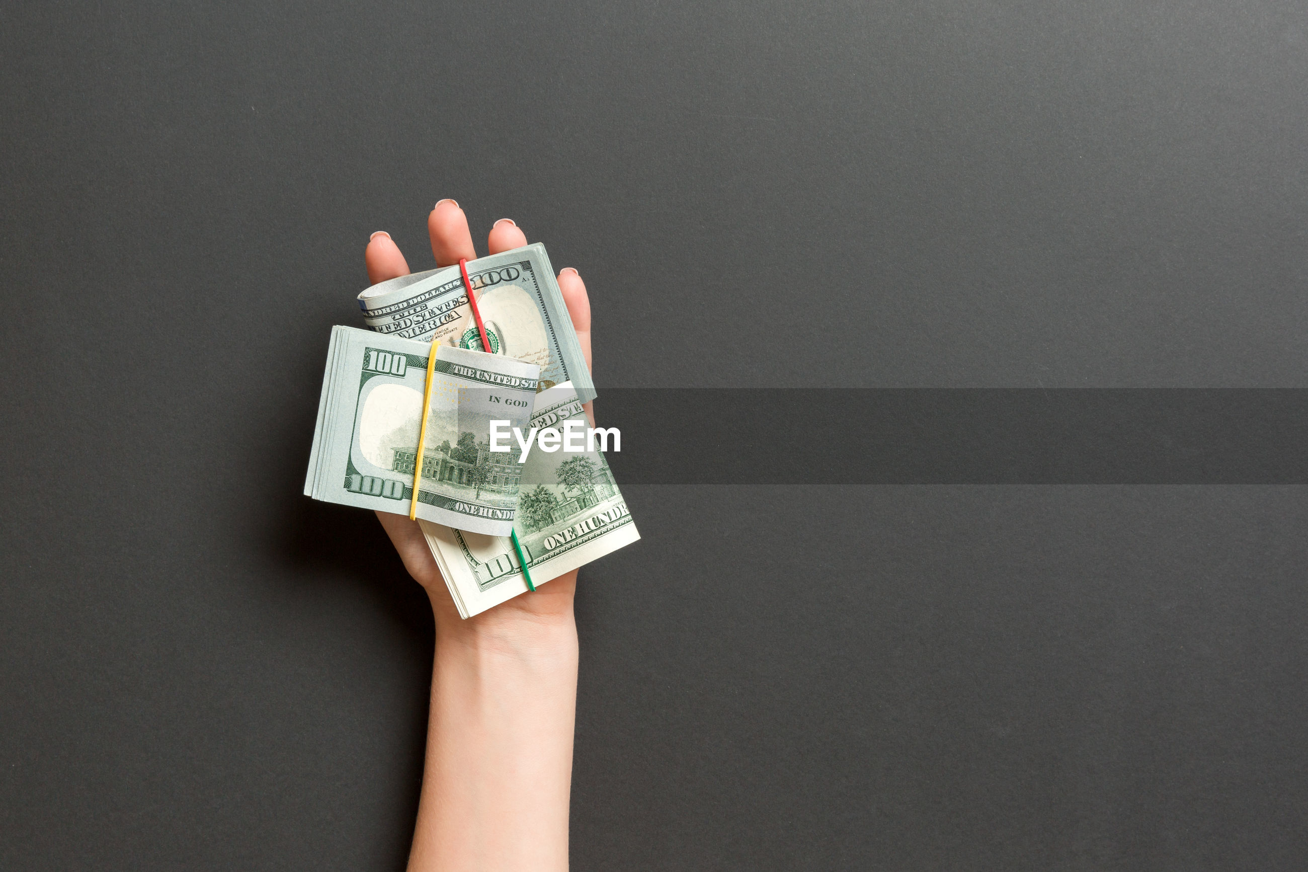 Cropped hands holding paper currencies on gray background