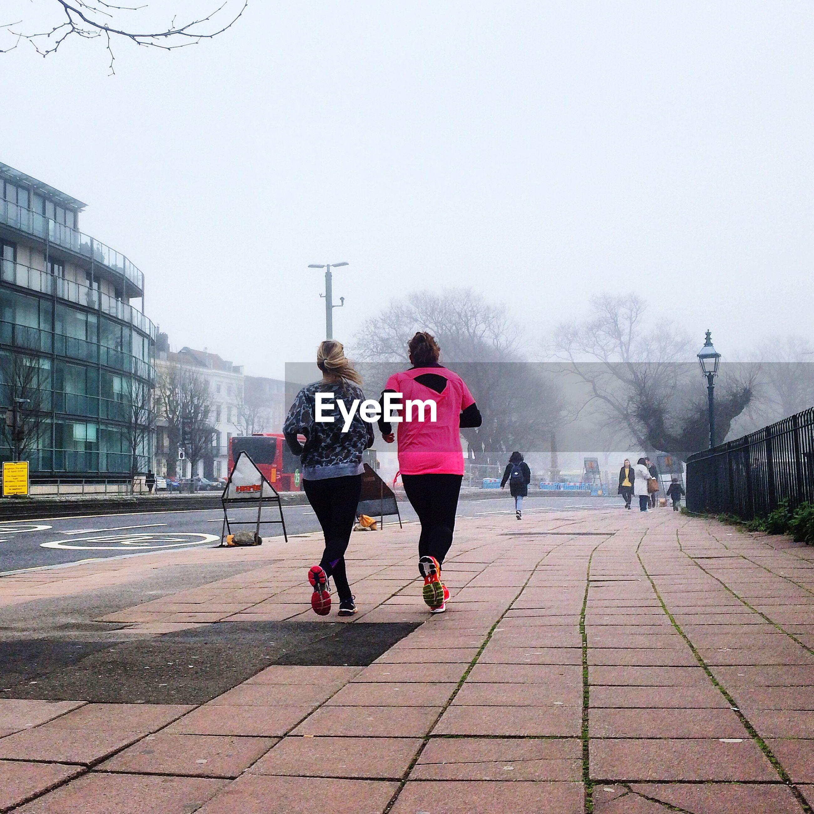 Two women jogging on sidewalk