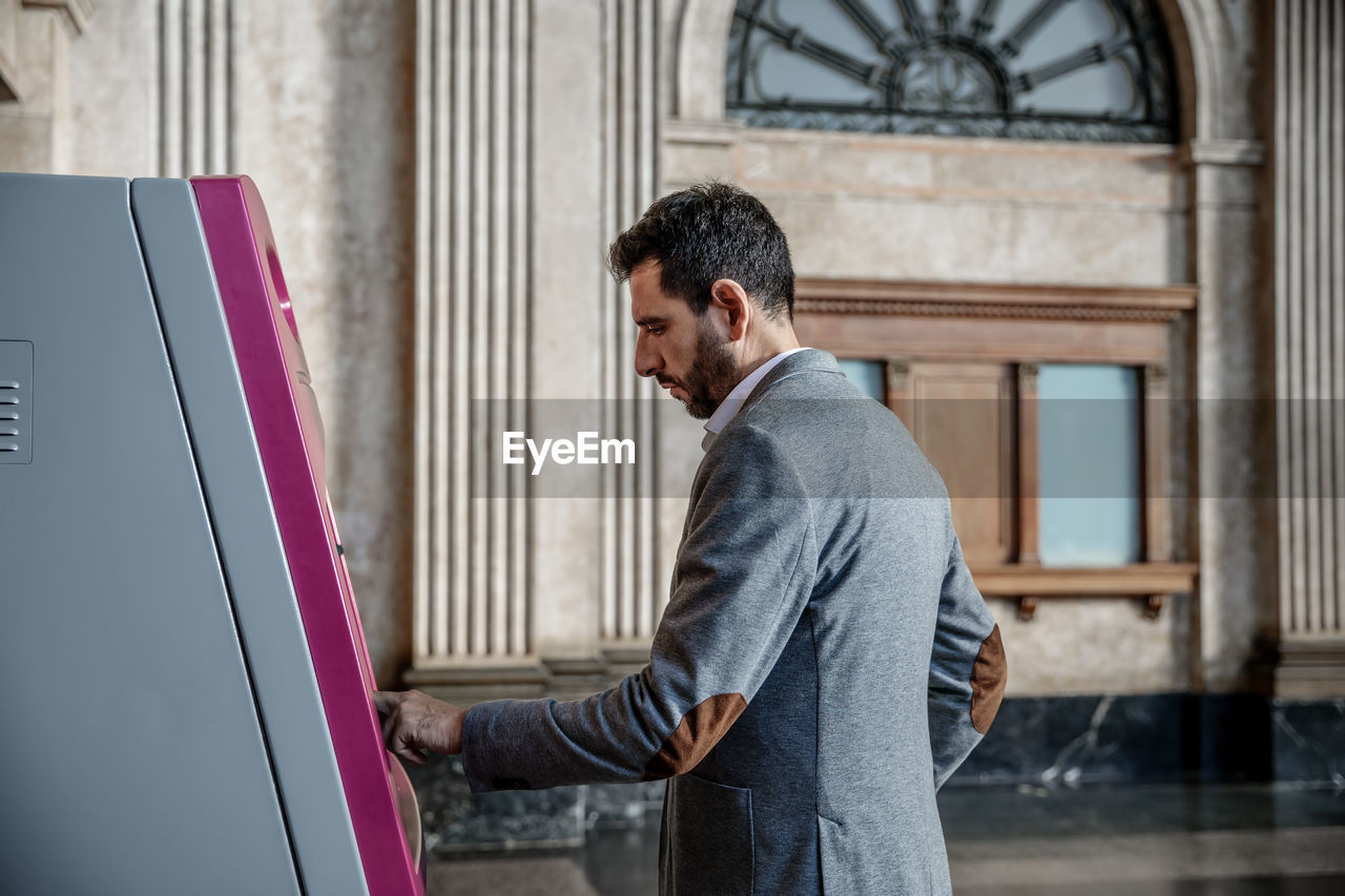 Man using atm machine in city