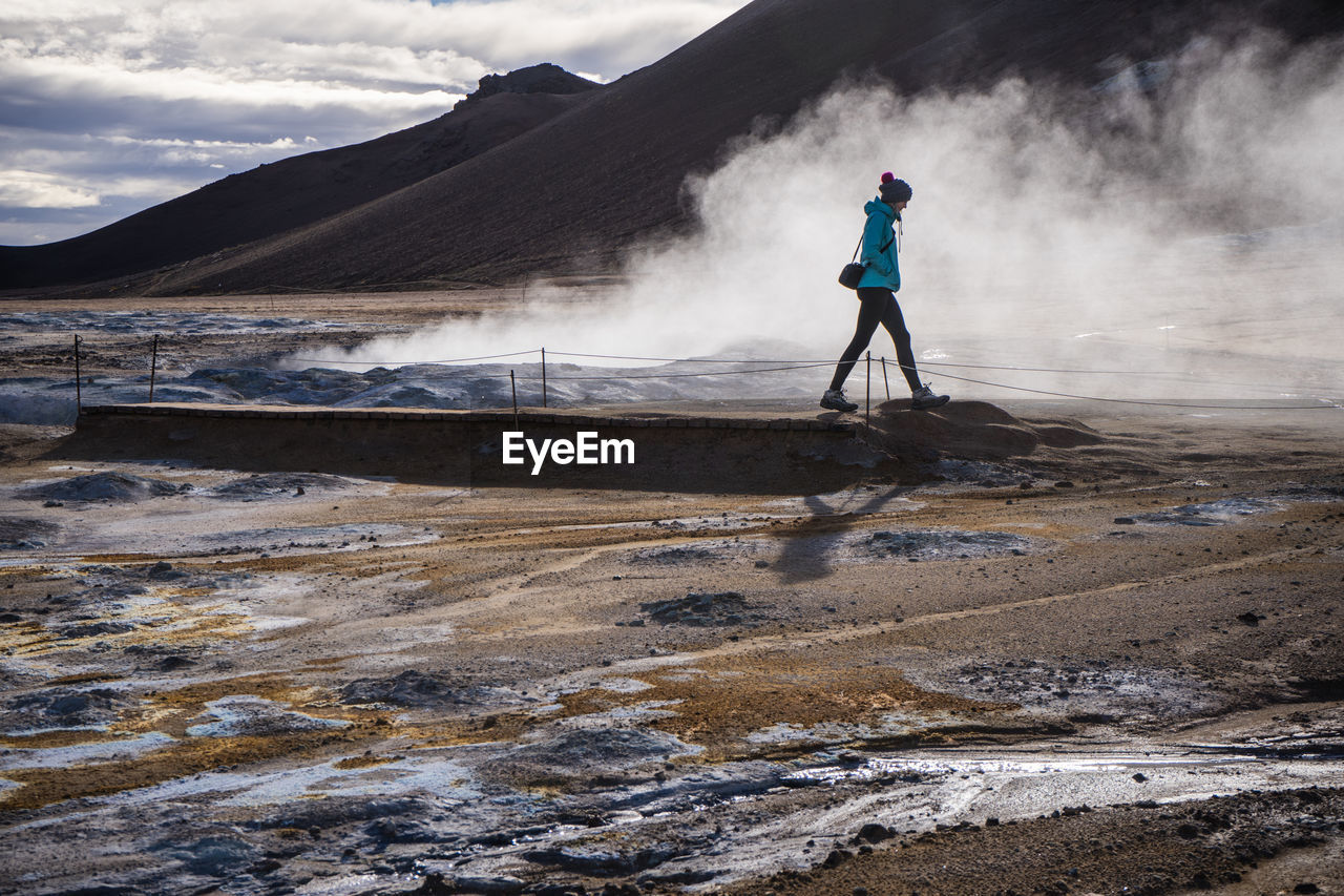 Woman Walking By Hot Spring Against Mountain