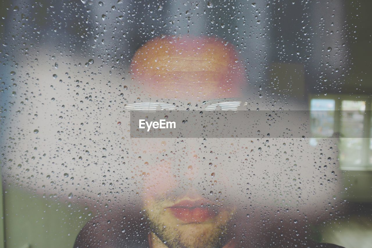 Close-Up Of Waterdrops On Glass A Man