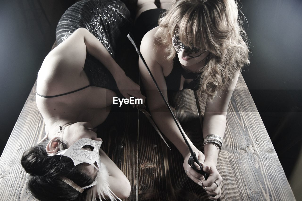High angle view of female friends wearing masks with whip and knife on table