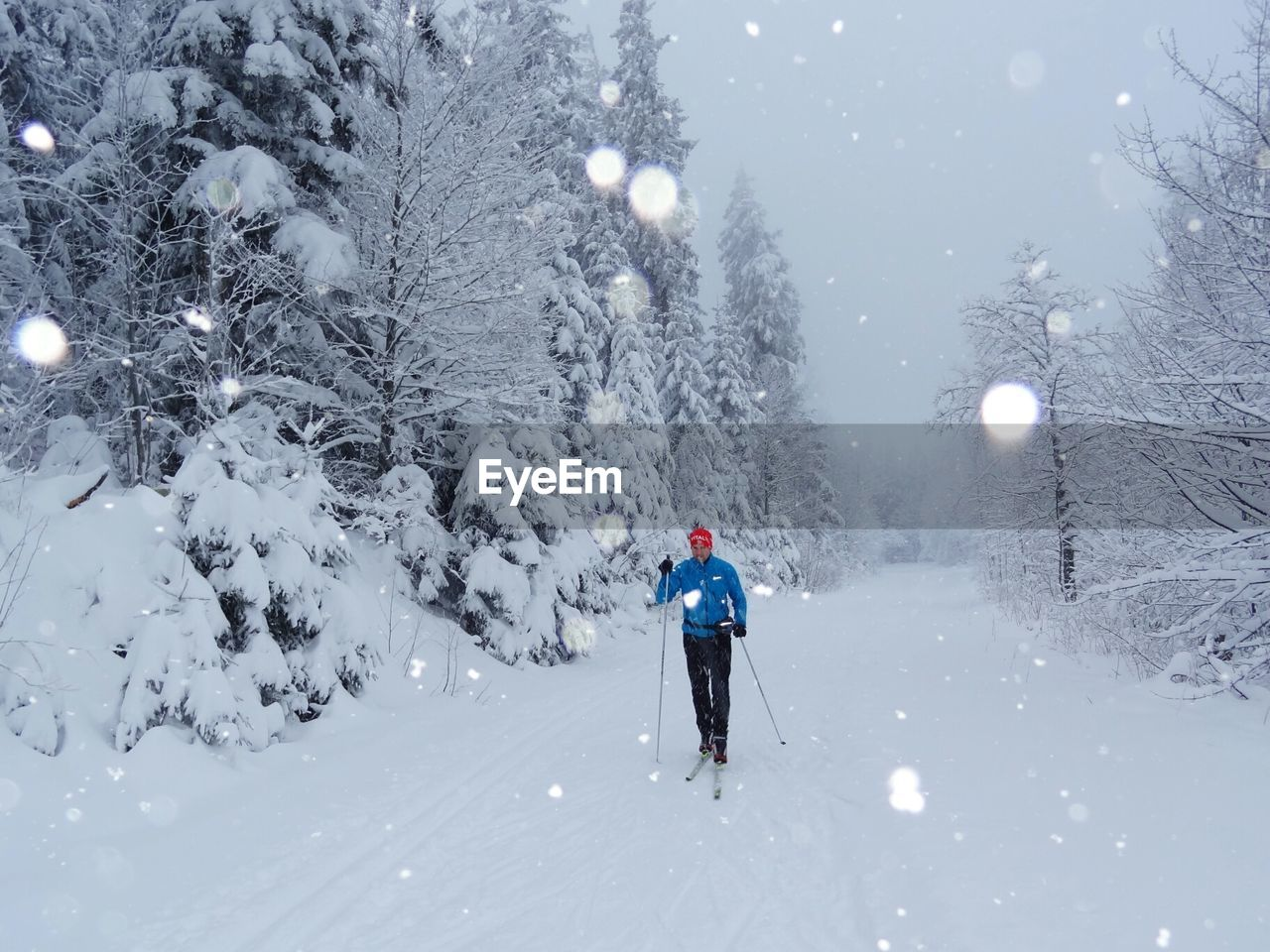Full length of man skiing on snow covered field during snow fall