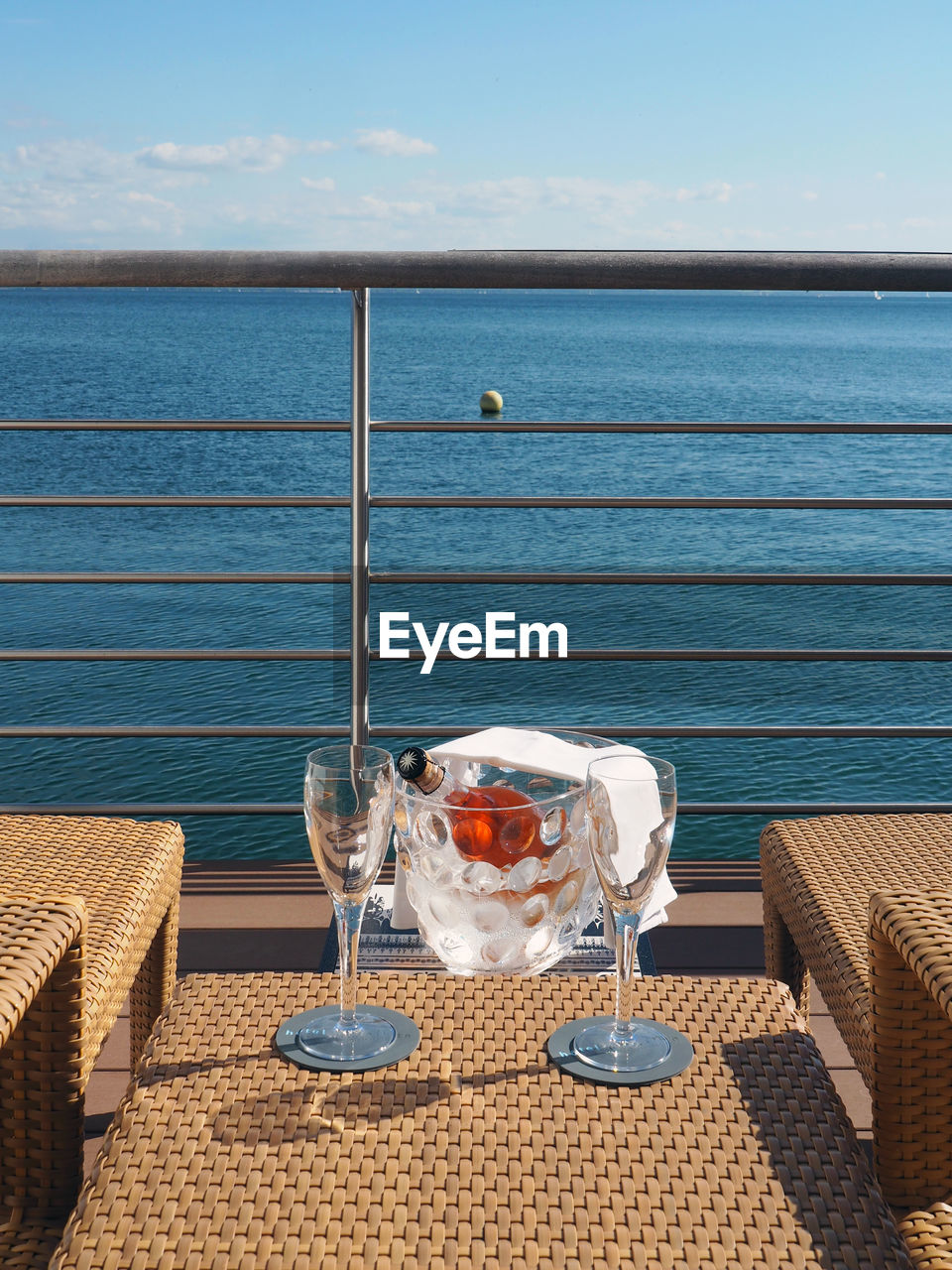 Champagne In Container By Flutes On Table In Balcony Against Sky