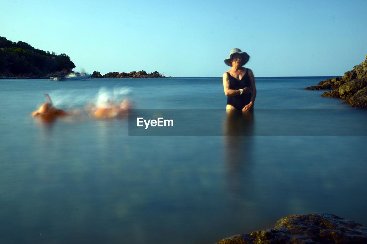 Senior Woman In Sea Against Clear Blue Sky