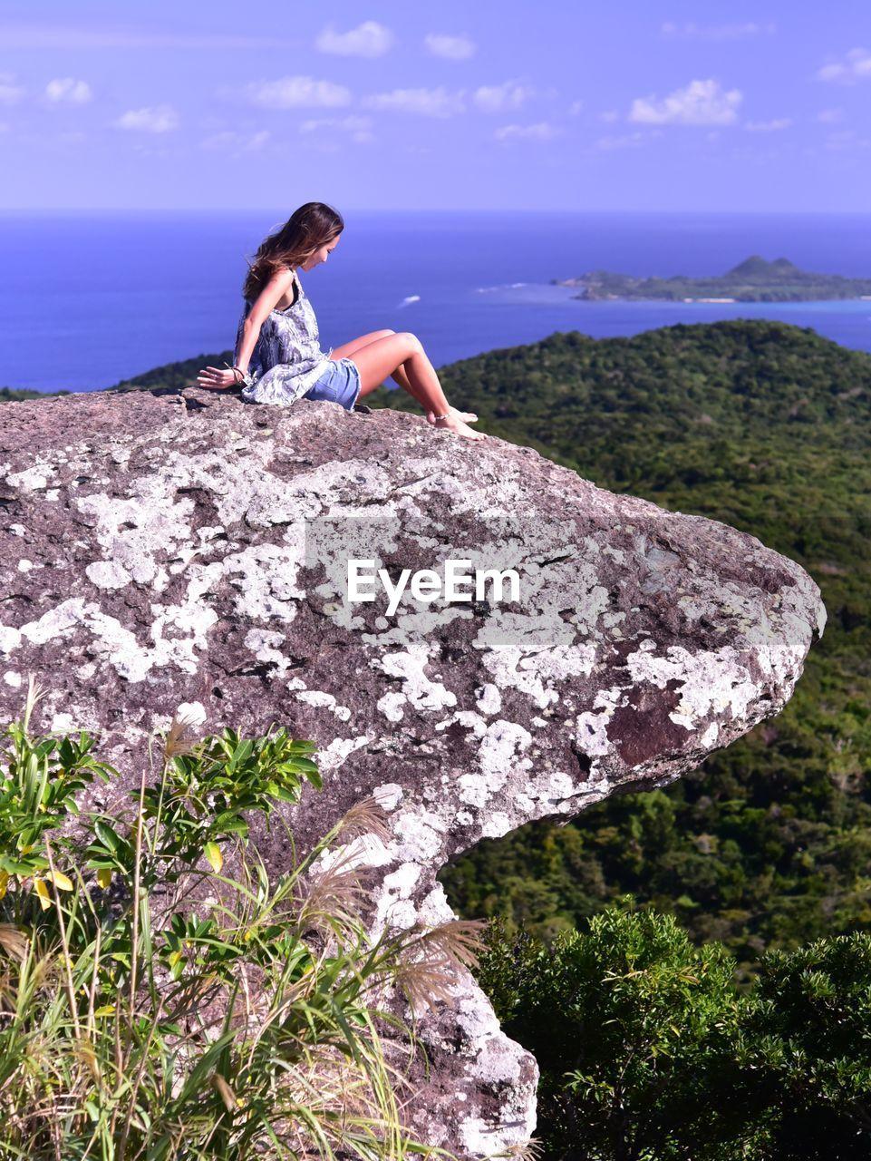 WOMAN SITTING ON ROCKS BY SEA AGAINST SKY