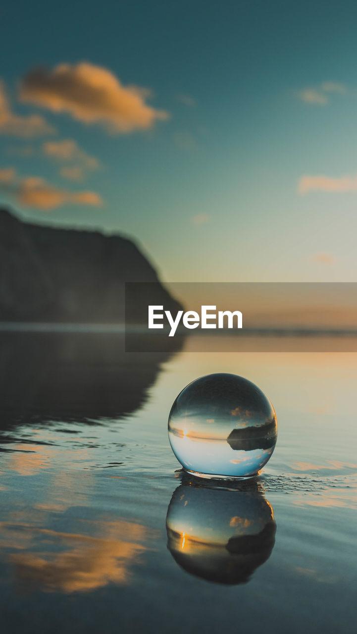 Lensball on beach against sky during sunset