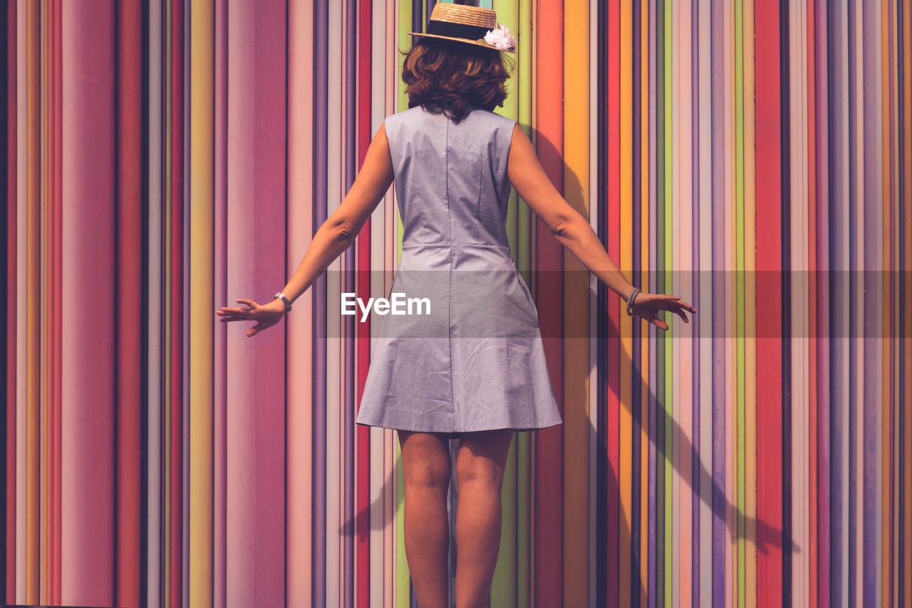 Rear View Of A Woman With Multi Colored Curtain
