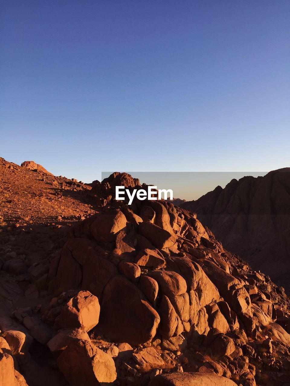 sky, rock, clear sky, scenics - nature, copy space, rock - object, beauty in nature, solid, tranquility, nature, tranquil scene, mountain, rock formation, landscape, sunlight, no people, environment, non-urban scene, arid climate, geology, climate, mountain range, outdoors, formation, eroded