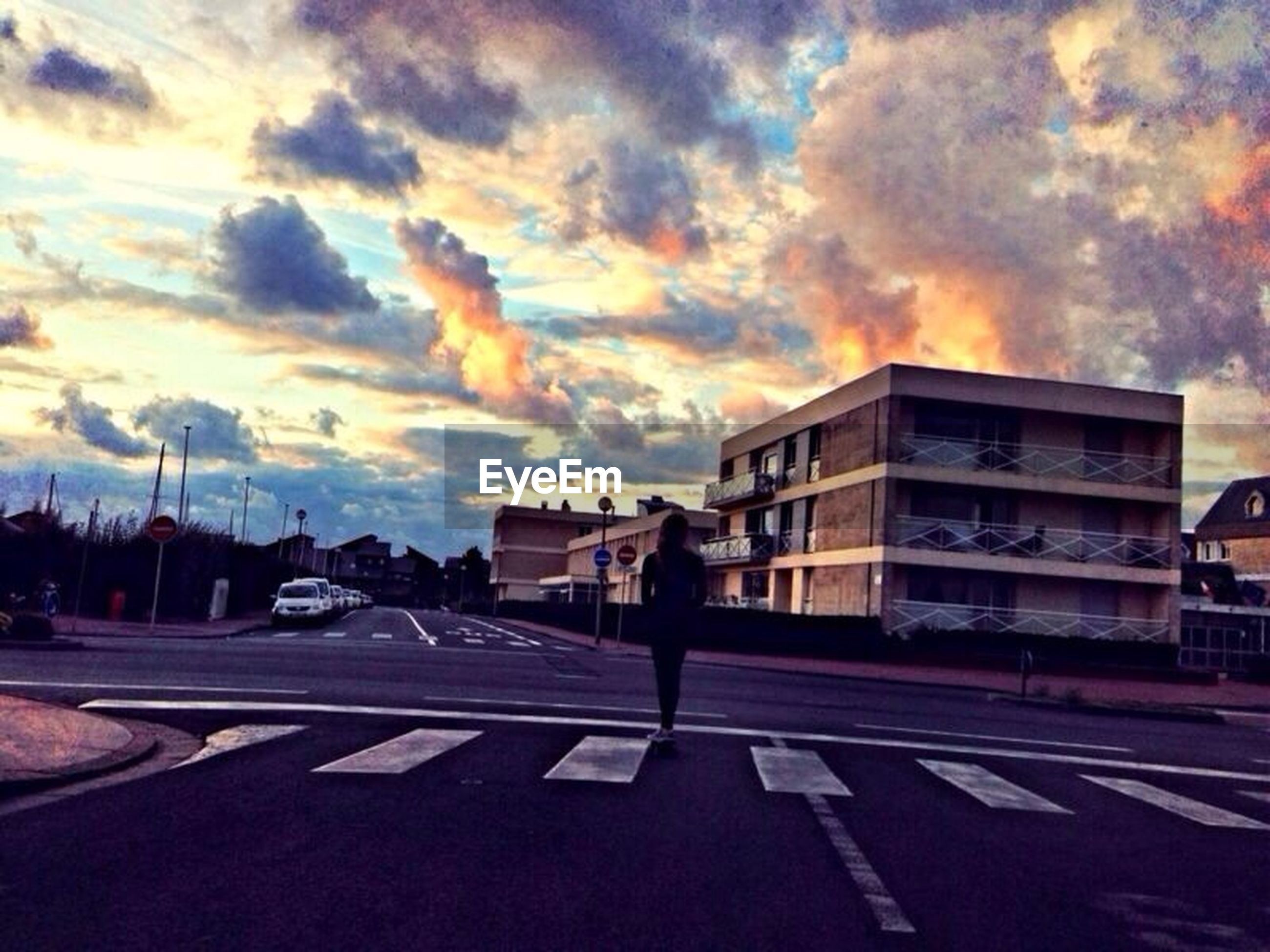 sky, cloud - sky, building exterior, transportation, street, road, architecture, car, built structure, land vehicle, cloudy, mode of transport, cloud, sunset, men, lifestyles, road marking, weather