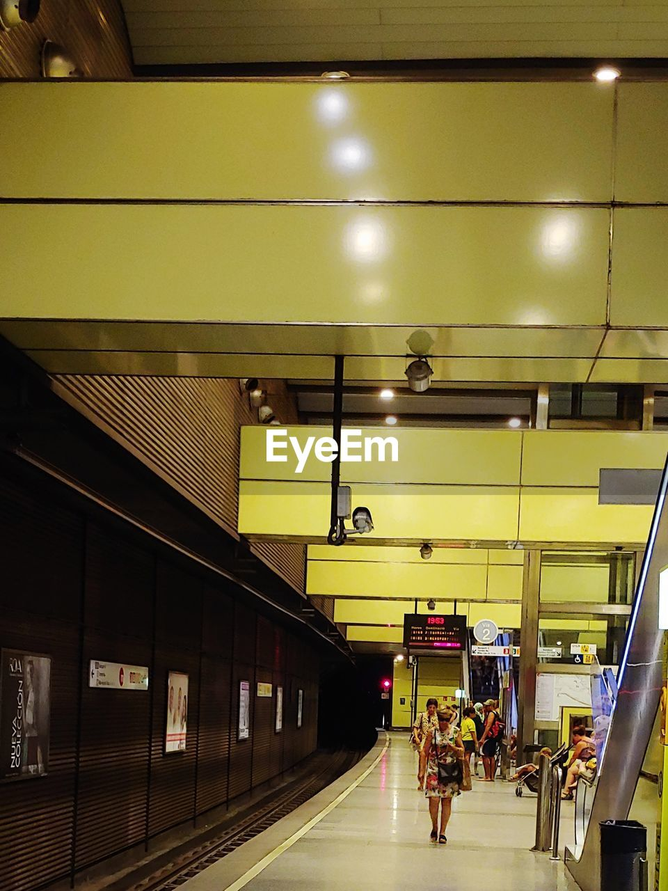 transportation, public transportation, indoors, rail transportation, architecture, mode of transportation, illuminated, subway station, real people, lighting equipment, travel, ceiling, men, group of people, lifestyles, built structure, incidental people, modern, light, waiting