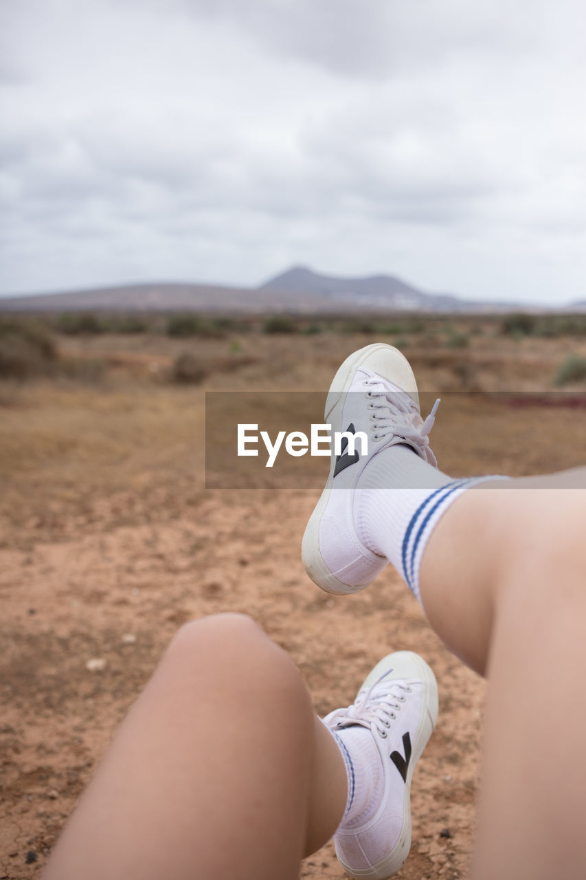 one person, human body part, sky, real people, human leg, day, low section, land, nature, lifestyles, body part, personal perspective, leisure activity, shoe, cloud - sky, landscape, environment, outdoors, focus on foreground, human foot, human limb, shorts