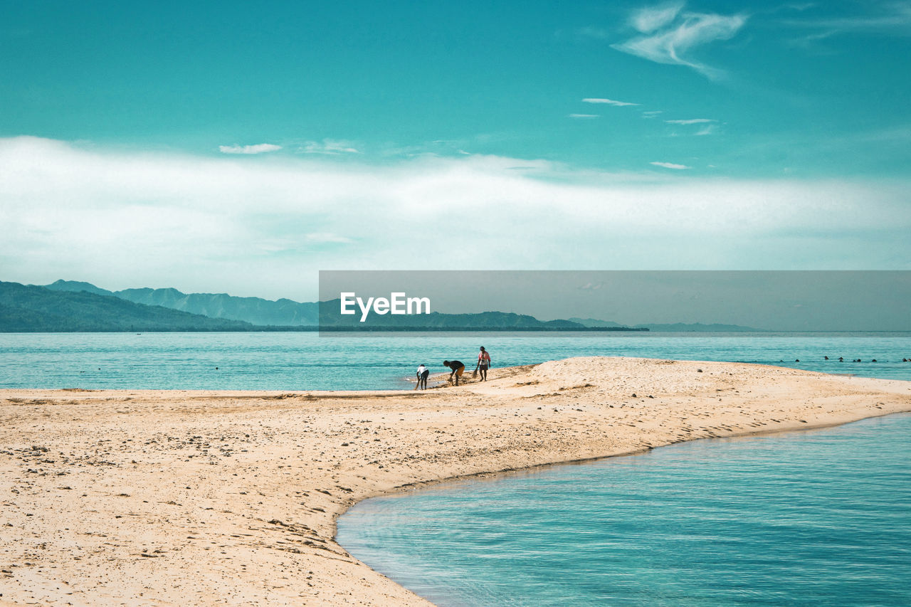 water, sea, land, beach, sky, horizon, ocean, body of water, scenics - nature, shore, nature, beauty in nature, sand, cloud, holiday, vacation, trip, travel, travel destinations, wave, coast, blue, tranquility, environment, tranquil scene, landscape, tourism, two people, coastline, summer, day, bay, water's edge, outdoors, adult, wind wave, relaxation, men, leisure activity, mountain, idyllic, sunlight, non-urban scene, island, tourist, seascape, horizon over water, full length