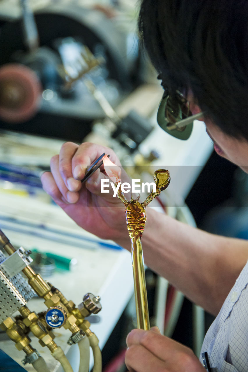skill, real people, indoors, working, craft, holding, occupation, one person, workshop, art and craft, adult, human hand, expertise, jewelry, hand, human body part, headshot, women, craftsperson, tweezers, precious gem