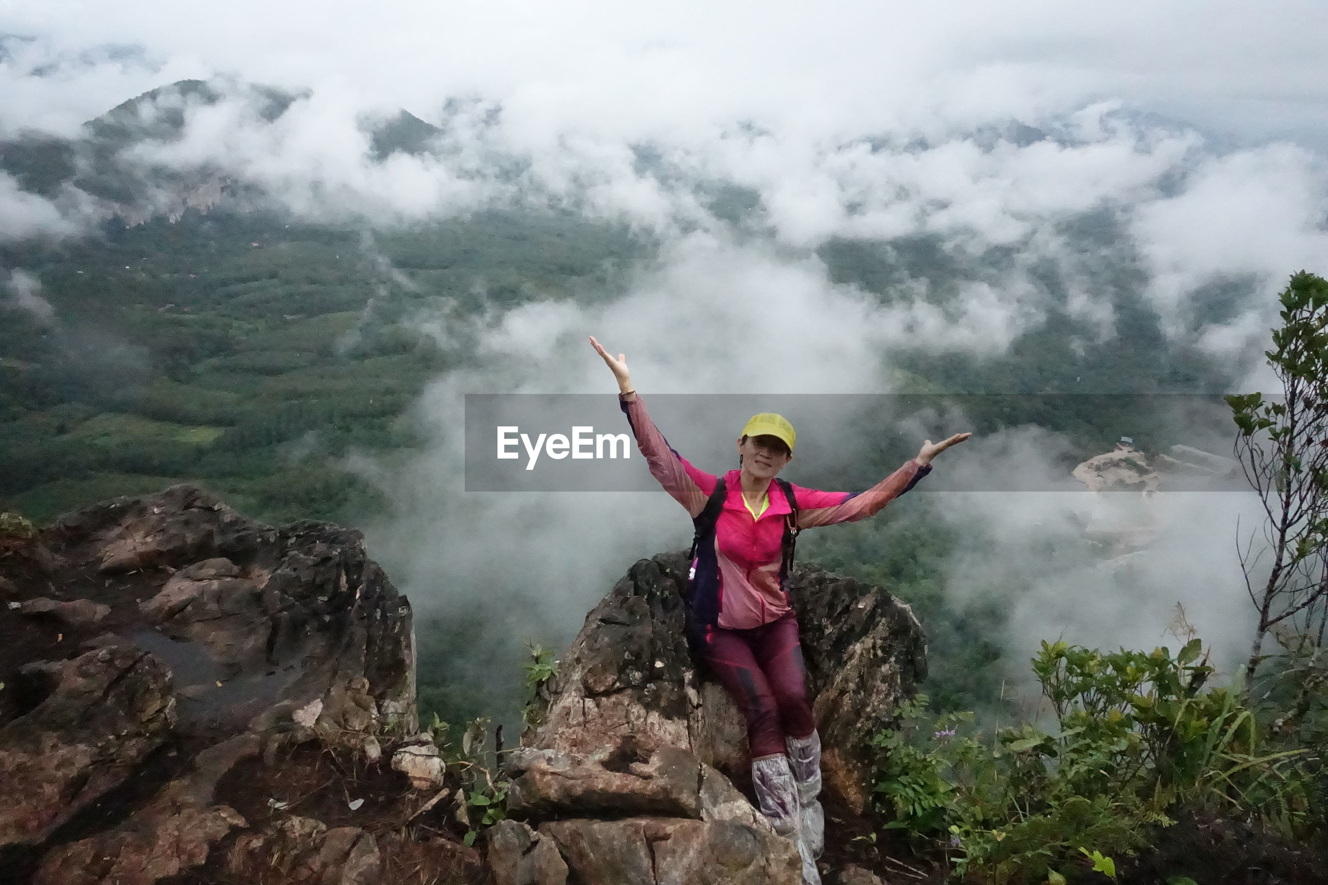 High angle view of female hiker sitting on rock with arms outstretched at mountain peak