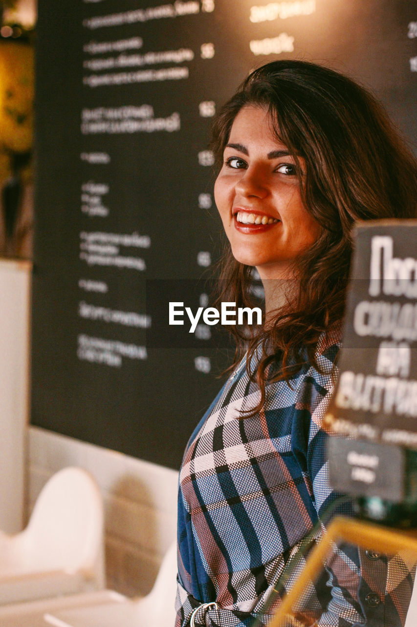 Portrait of a smiling young woman at restaurant