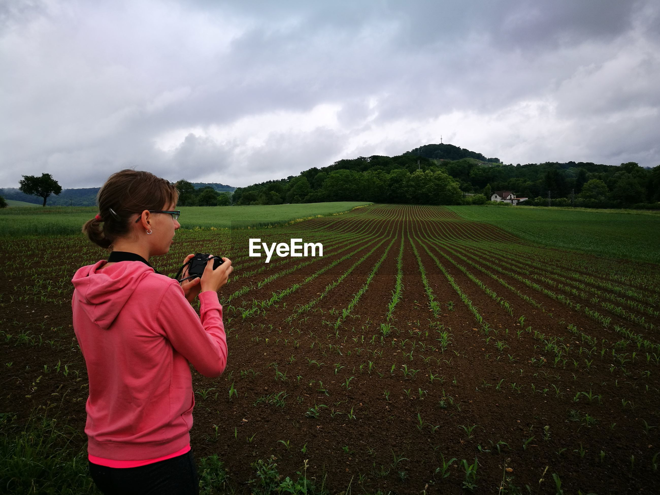 Woman photographing agricultural field against cloudy sky