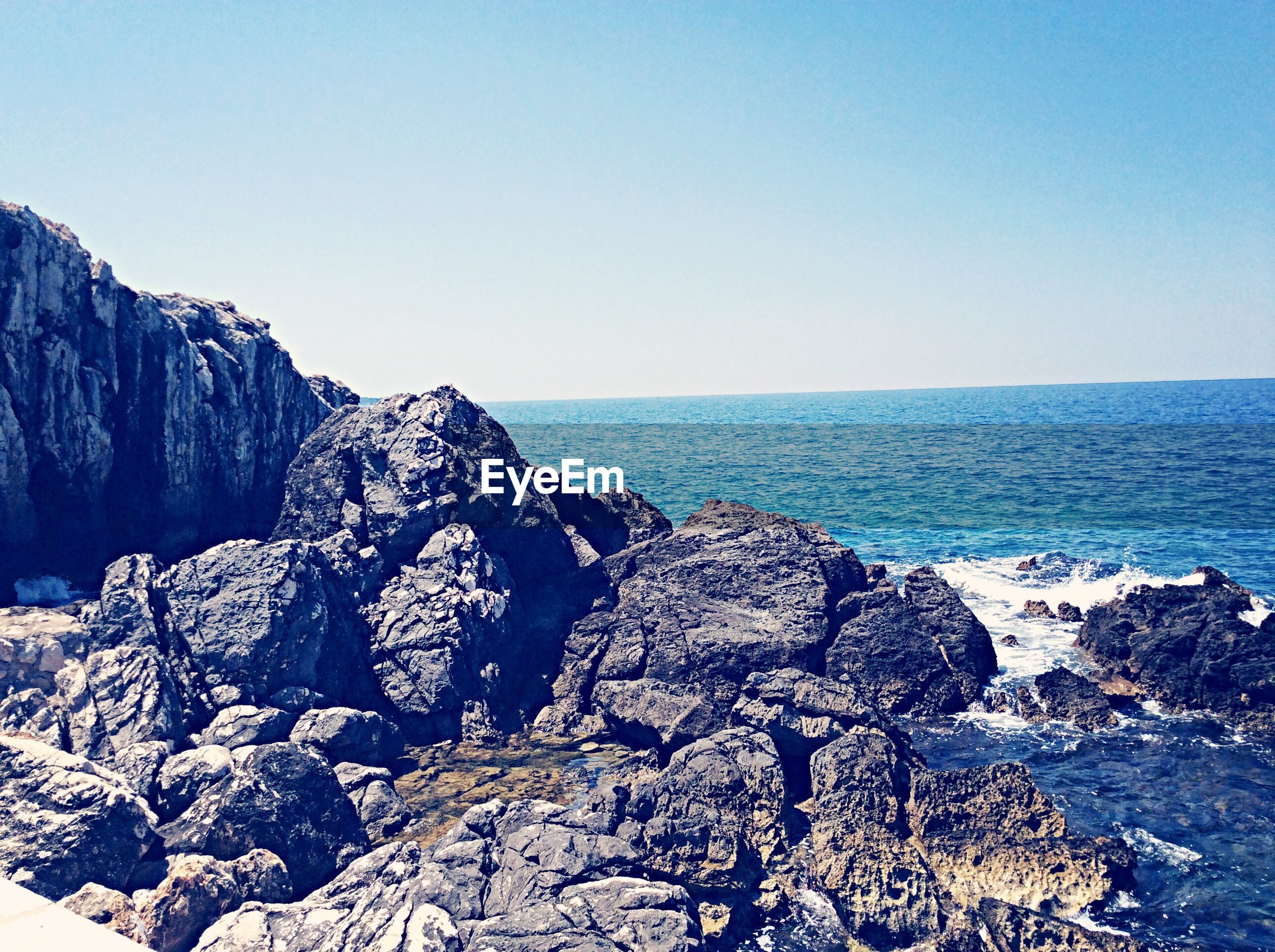 water, sea, scenics, blue, clear sky, beauty in nature, rock formation, tranquility, tranquil scene, rock - object, nature, mountain, copy space, idyllic, cliff, geology, rock, waterfront, non-urban scene, day
