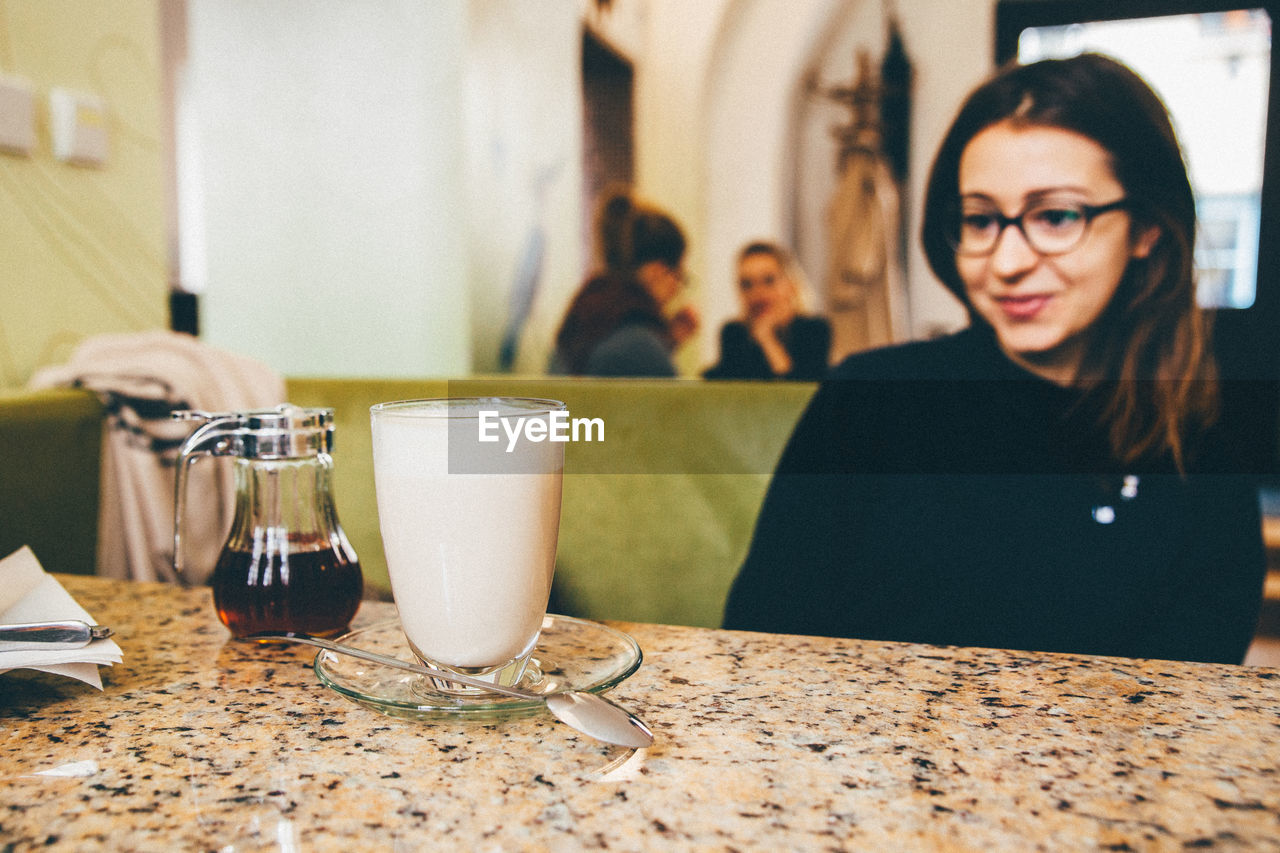 table, real people, indoors, eyeglasses, food and drink, drink, one person, women, lifestyles, drinking glass, sitting, close-up, freshness, day, young adult, people
