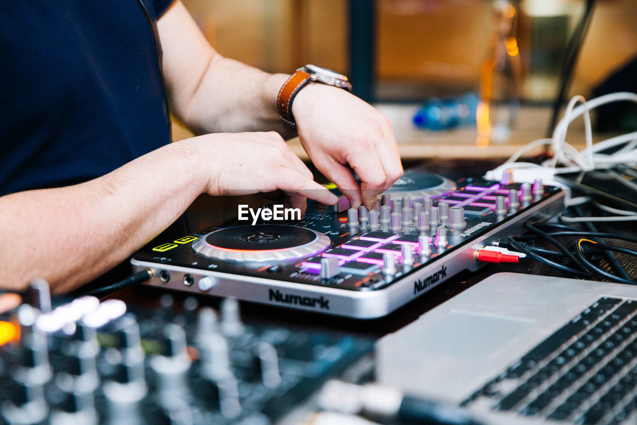 human hand, one person, real people, hand, technology, occupation, selective focus, human body part, music, audio equipment, indoors, sound recording equipment, sound mixer, men, control, midsection, arts culture and entertainment, skill, control panel, finger, mixing, human limb, nightlife, club dj