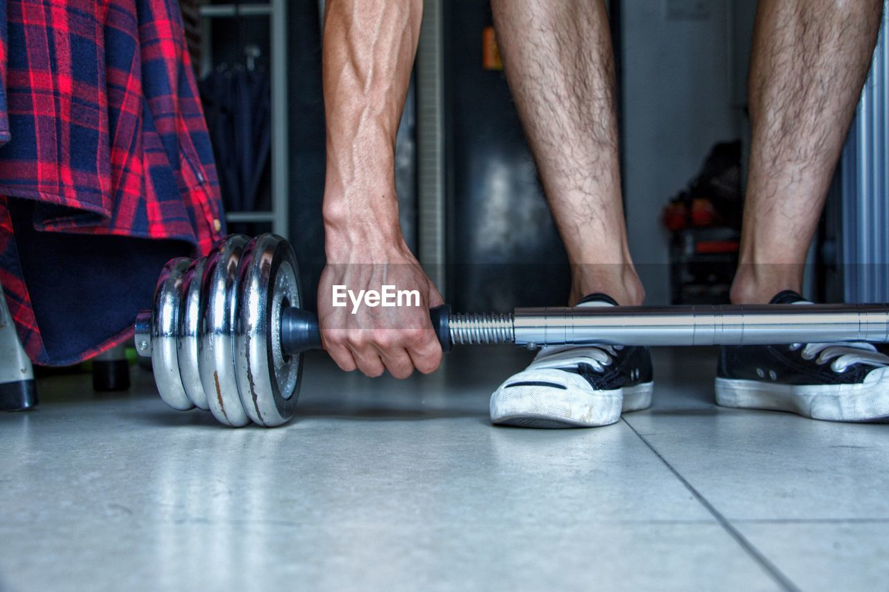 Low Section Of Man Lifting Dumbbell In Gym