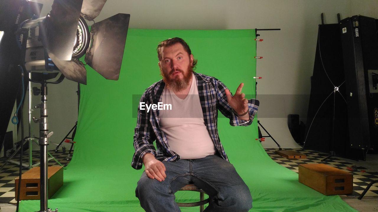 Portrait of man on seat in film studio