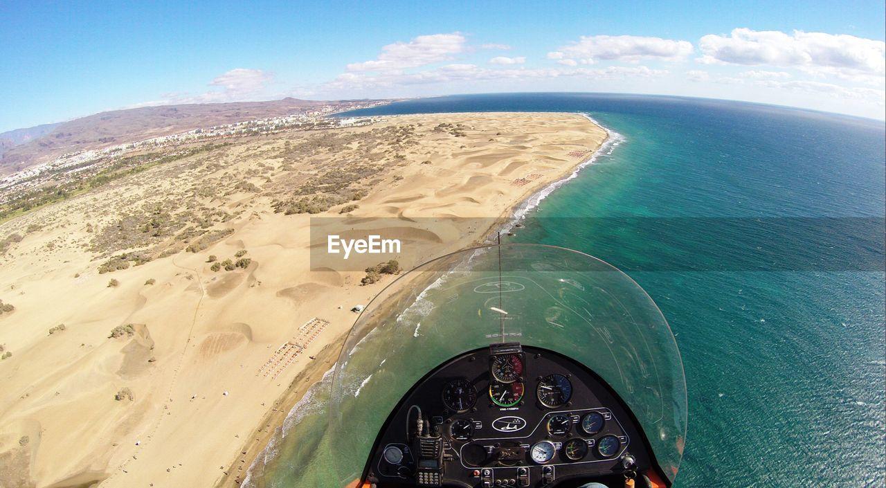Cropped image of gyrocopter flying over coastline against sky