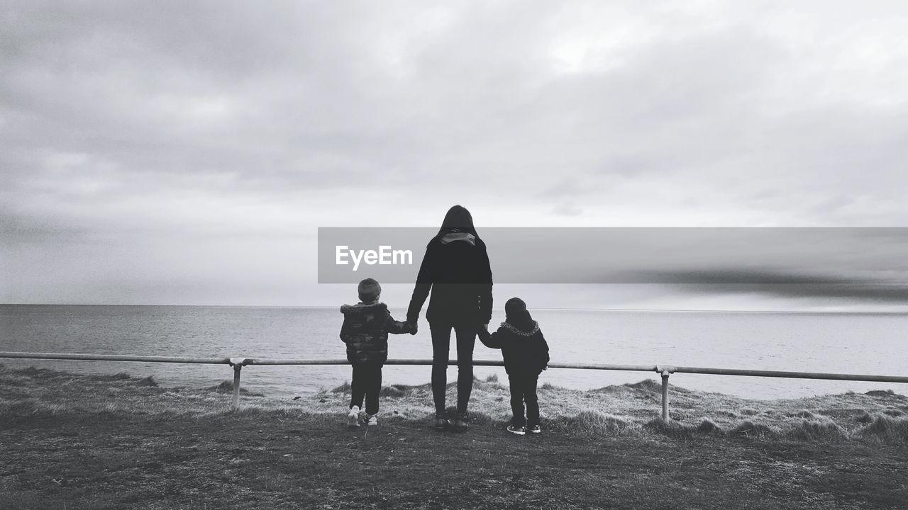 Rear View Of Mother With Sons Standing At Beach Against Sky