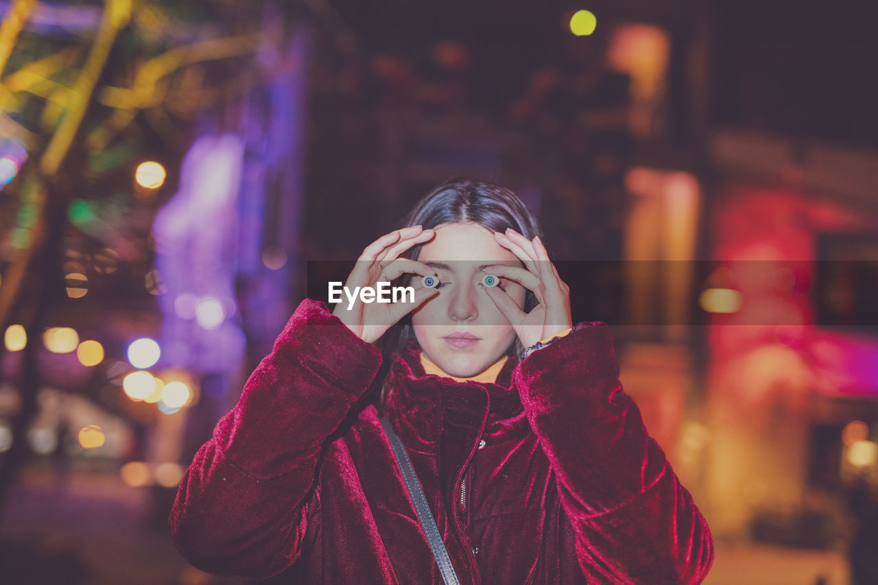 one person, front view, portrait, lifestyles, real people, focus on foreground, leisure activity, night, illuminated, headshot, clothing, warm clothing, winter, young adult, young women, standing, waist up, looking at camera, scarf, teenager