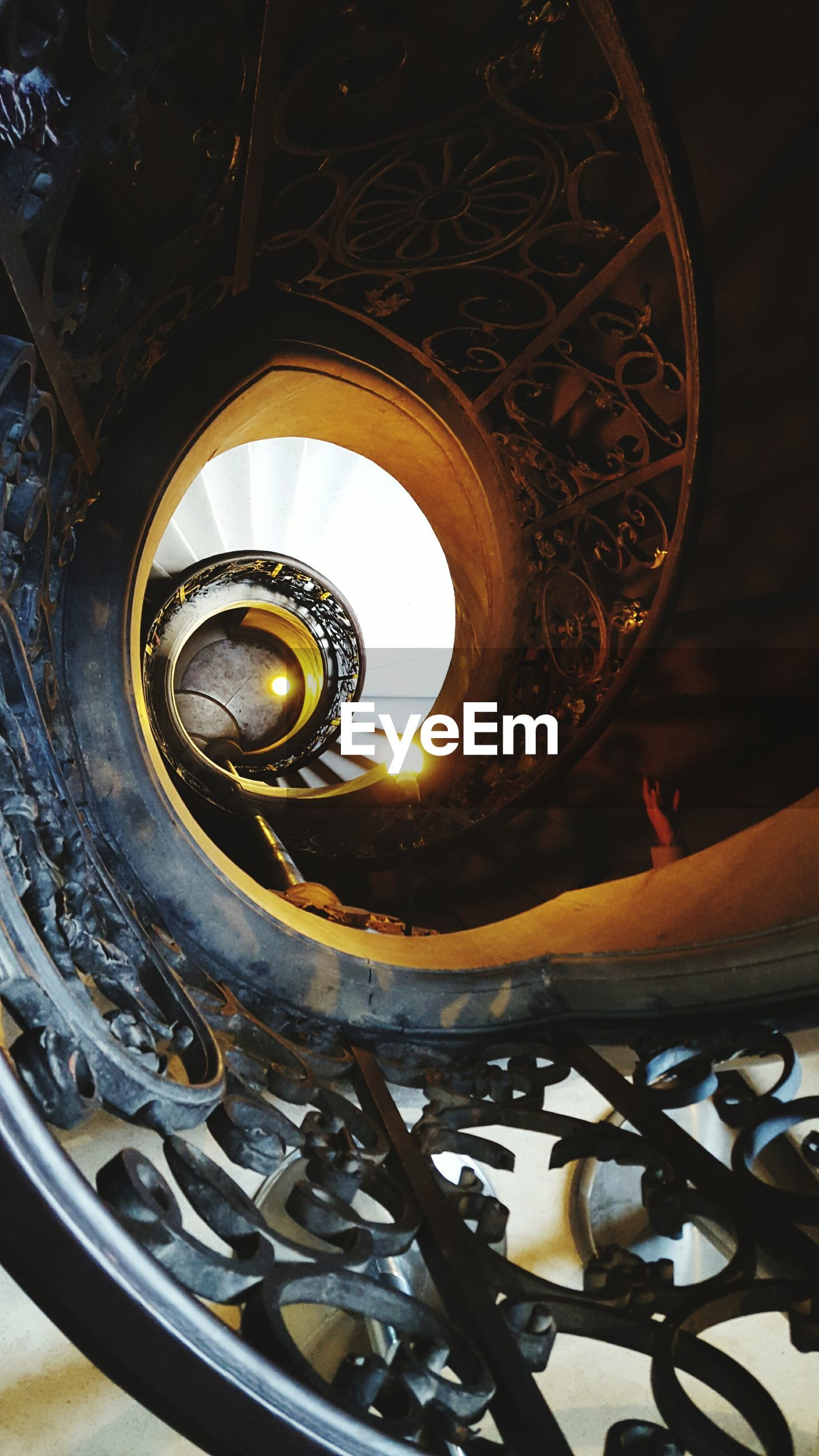 indoors, spiral, spiral staircase, circle, railing, metal, staircase, steps and staircases, steps, low angle view, design, wheel, directly below, part of, pattern, built structure, close-up, architecture, metallic, geometric shape