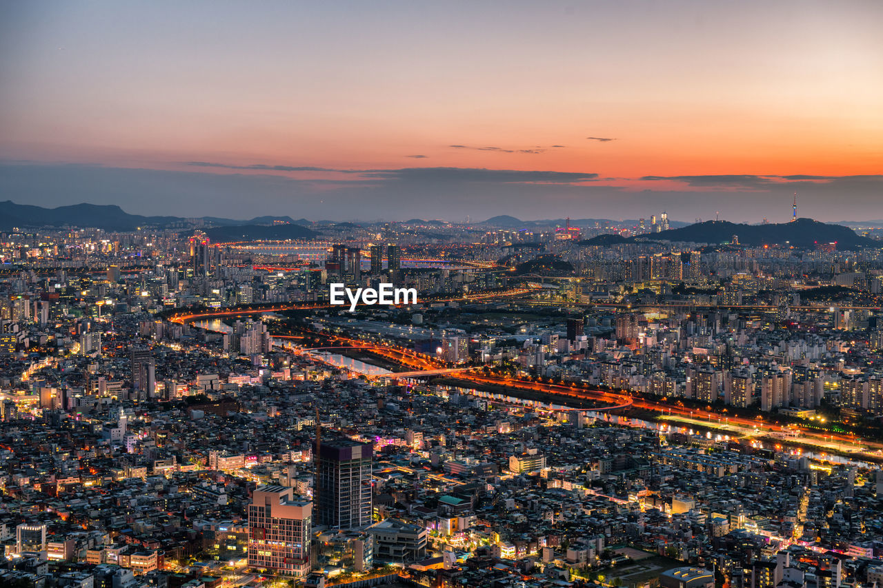 High angle view of illuminated cityscape sky during sunset