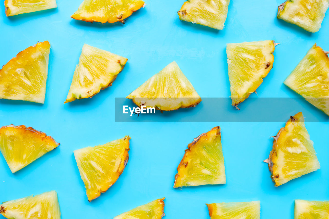 food and drink, food, no people, freshness, still life, indoors, yellow, large group of objects, healthy eating, slice, wellbeing, blue background, colored background, repetition, high angle view, arrangement, ready-to-eat, blue, close-up, full frame, snack, orange, chopped