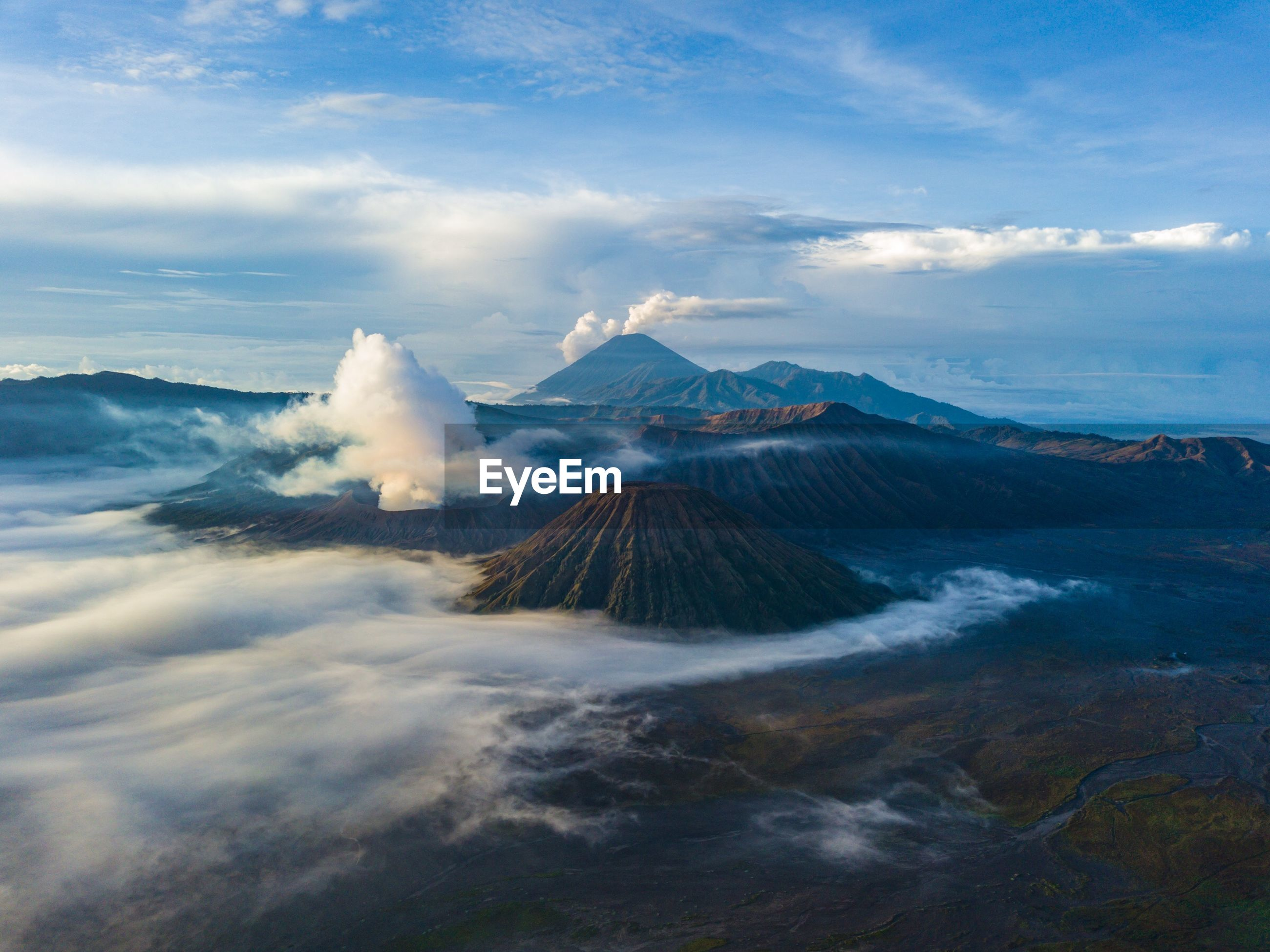 Smoke emitting from volcanic mountains against cloudy sky