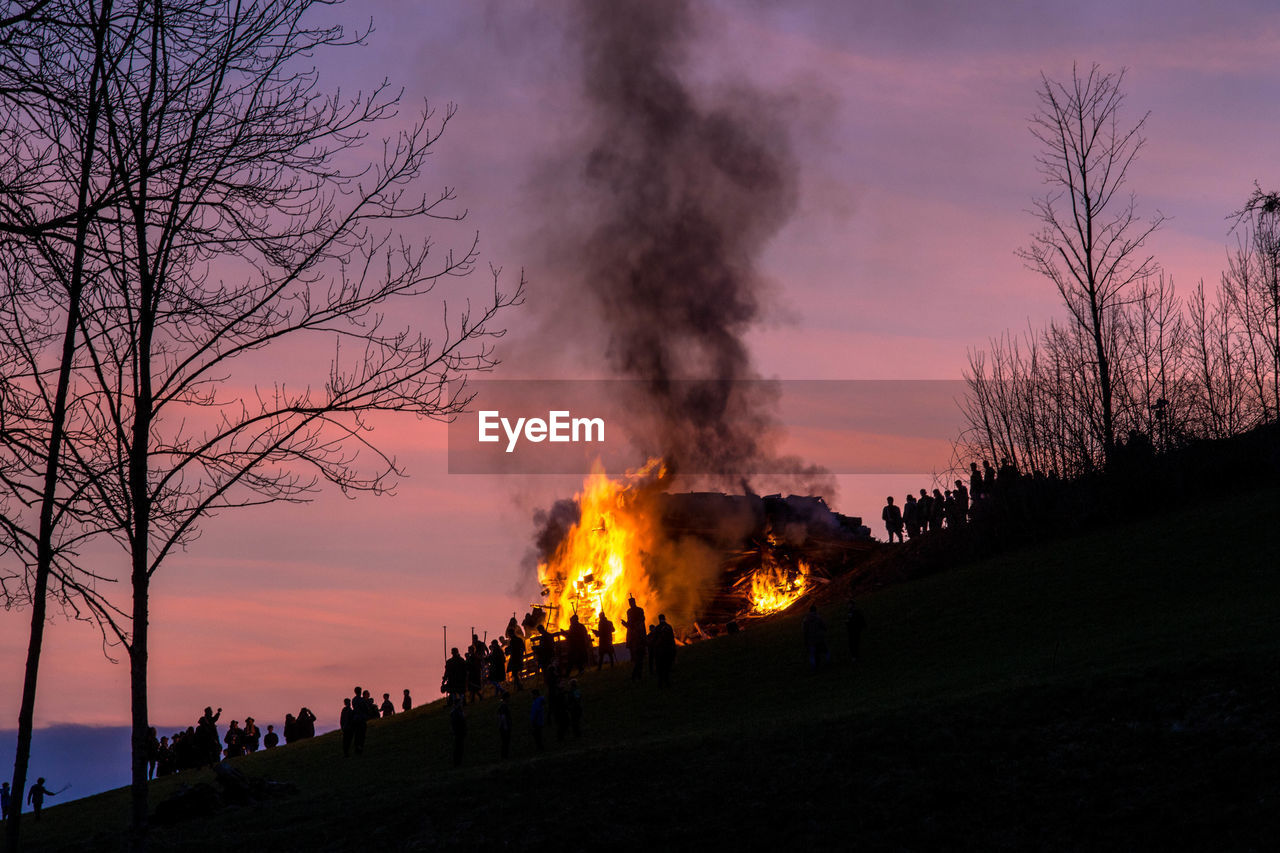 smoke - physical structure, flame, burning, tree, sky, fire, nature, fire - natural phenomenon, sunset, heat - temperature, accidents and disasters, orange color, bare tree, outdoors, architecture, silhouette, built structure, environment, plant, group of people