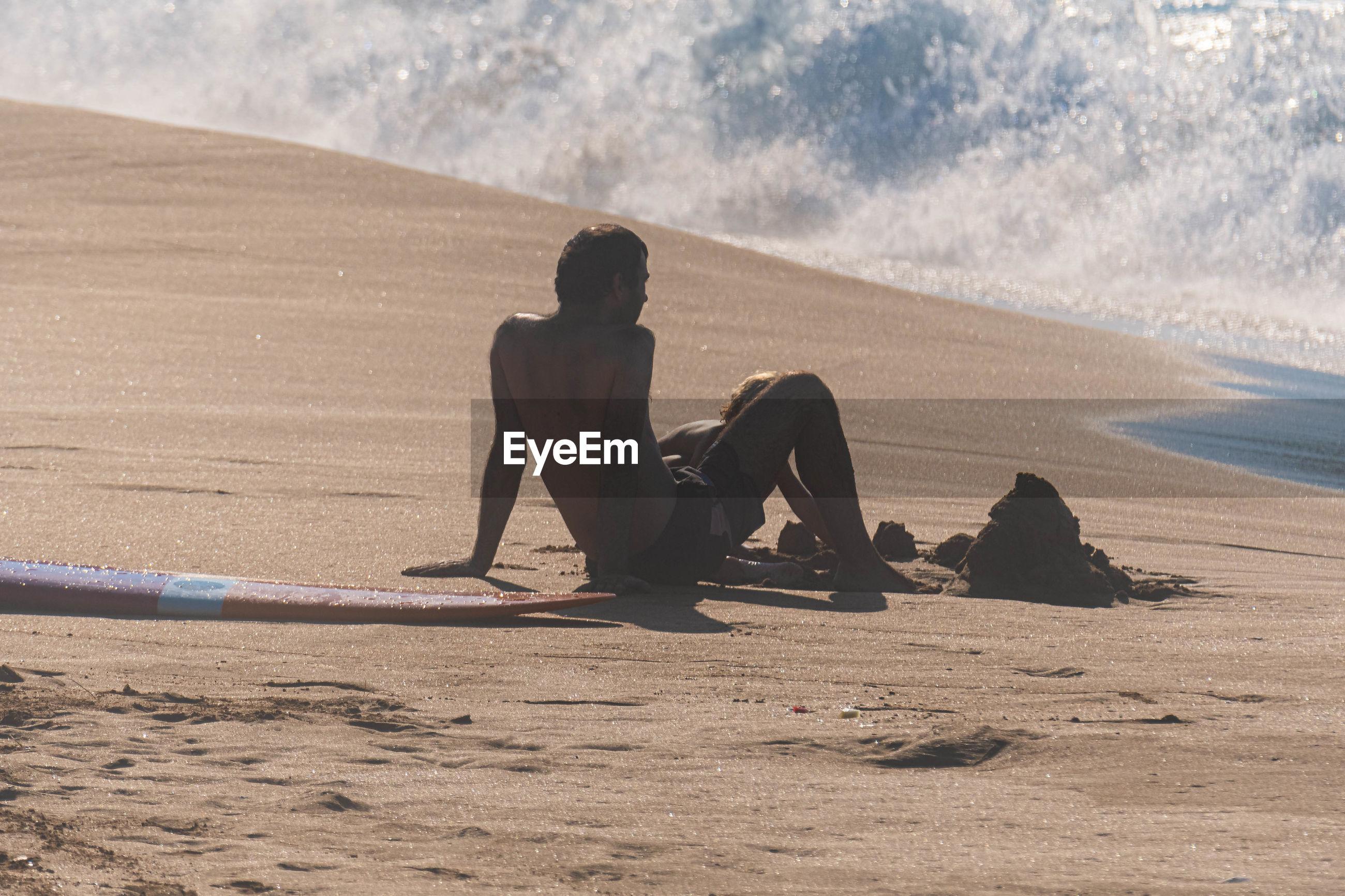 FULL LENGTH OF MAN SITTING ON SHORE AT BEACH
