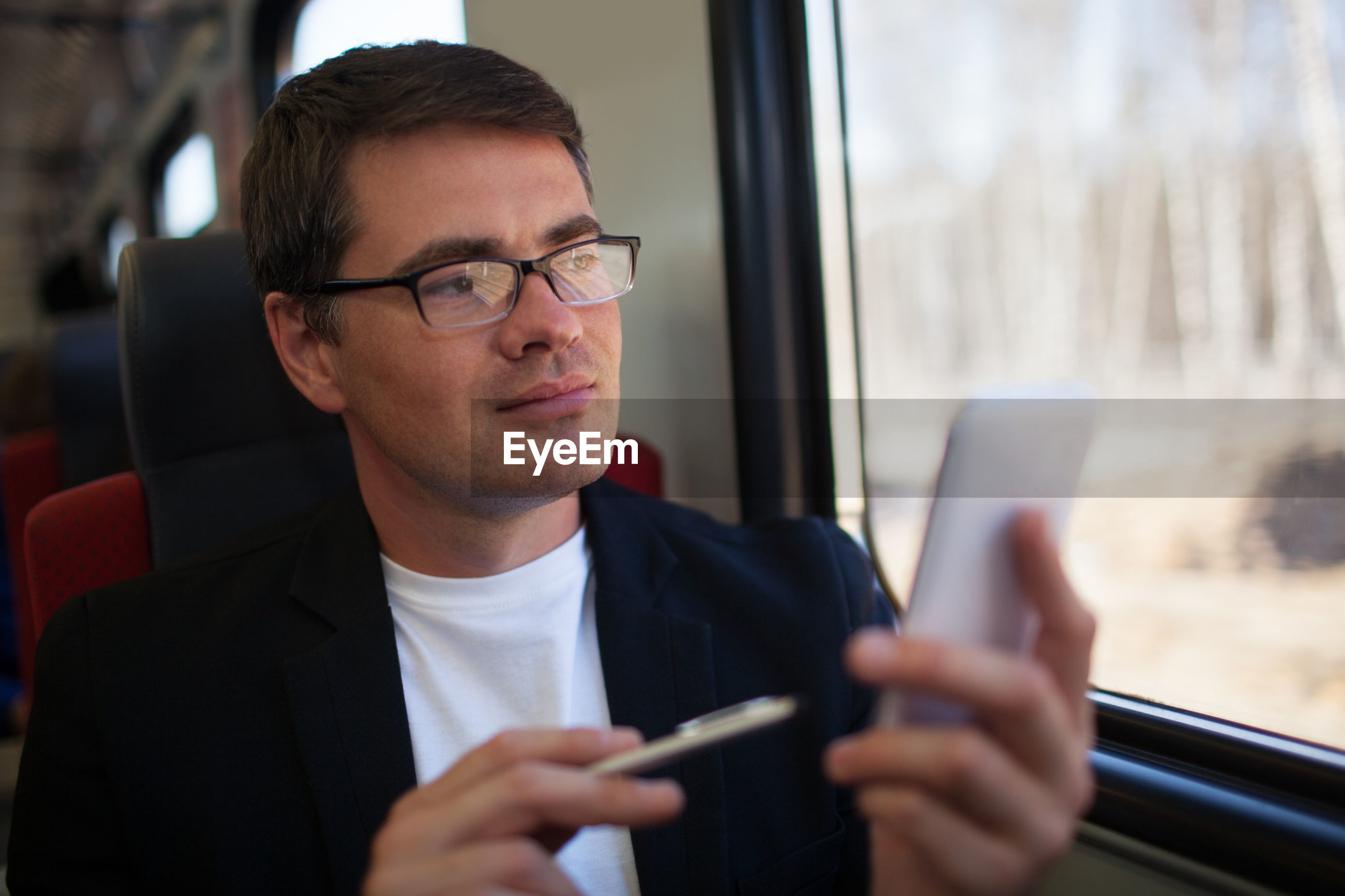 Businessman holding smart phone looking through window in train