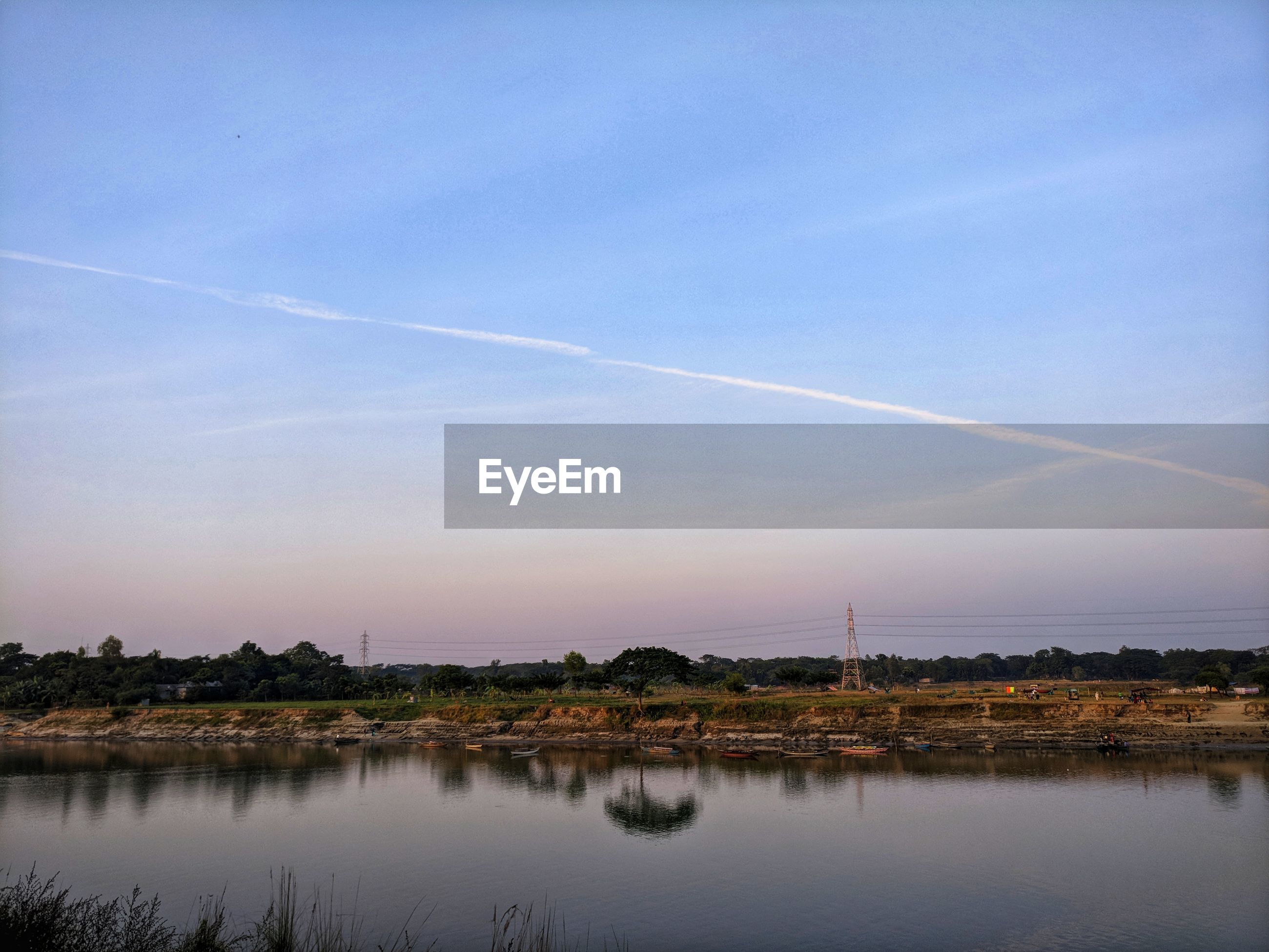 SCENIC VIEW OF LAKE AGAINST VAPOR TRAILS IN SKY