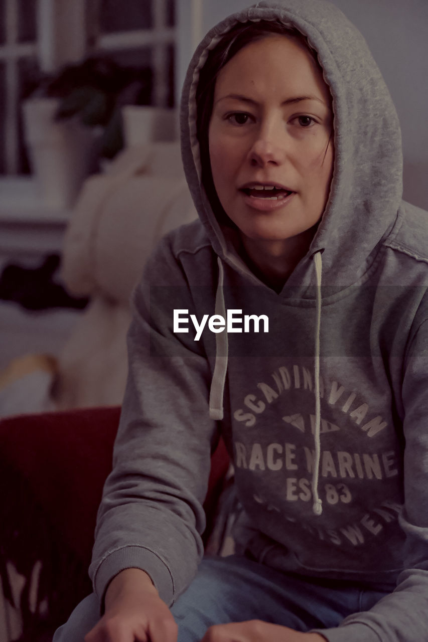 looking at camera, real people, one person, portrait, front view, indoors, sitting, lifestyles, smiling, casual clothing, women, three quarter length, hood, clothing, females, leisure activity, waist up, focus on foreground, hood - clothing
