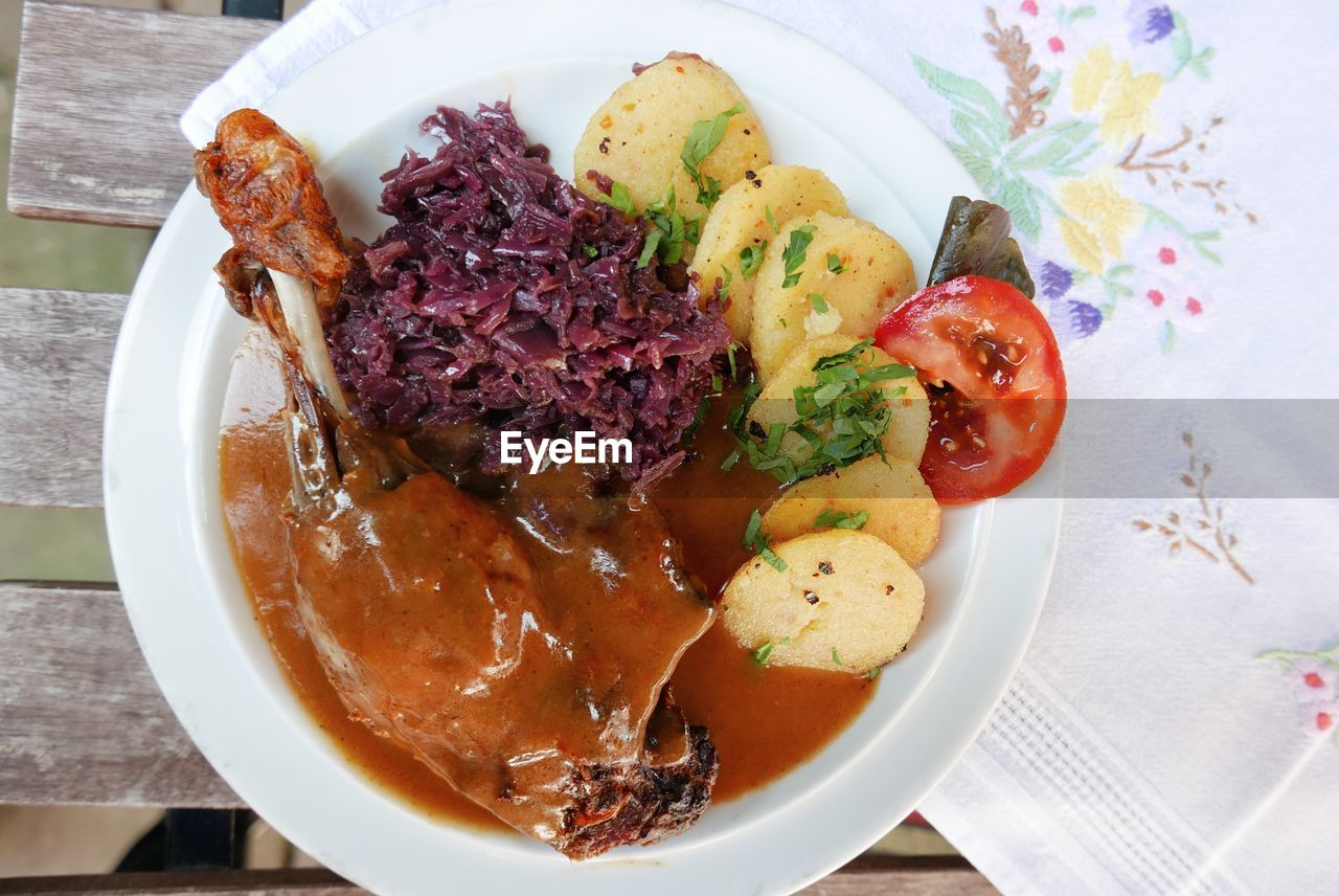 High angle view of meat served by cabbage and potatoes in plate on table