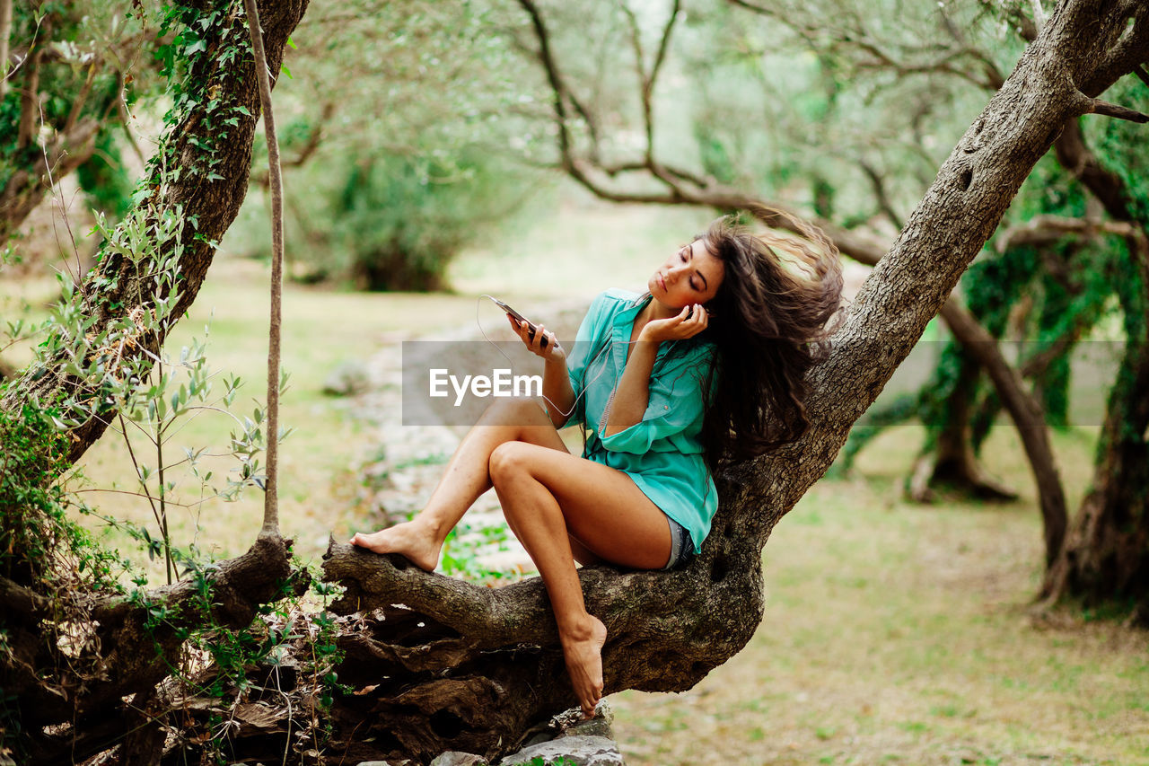 Beautiful Woman Listening Music On Headphones While Sitting On Tree In Forest