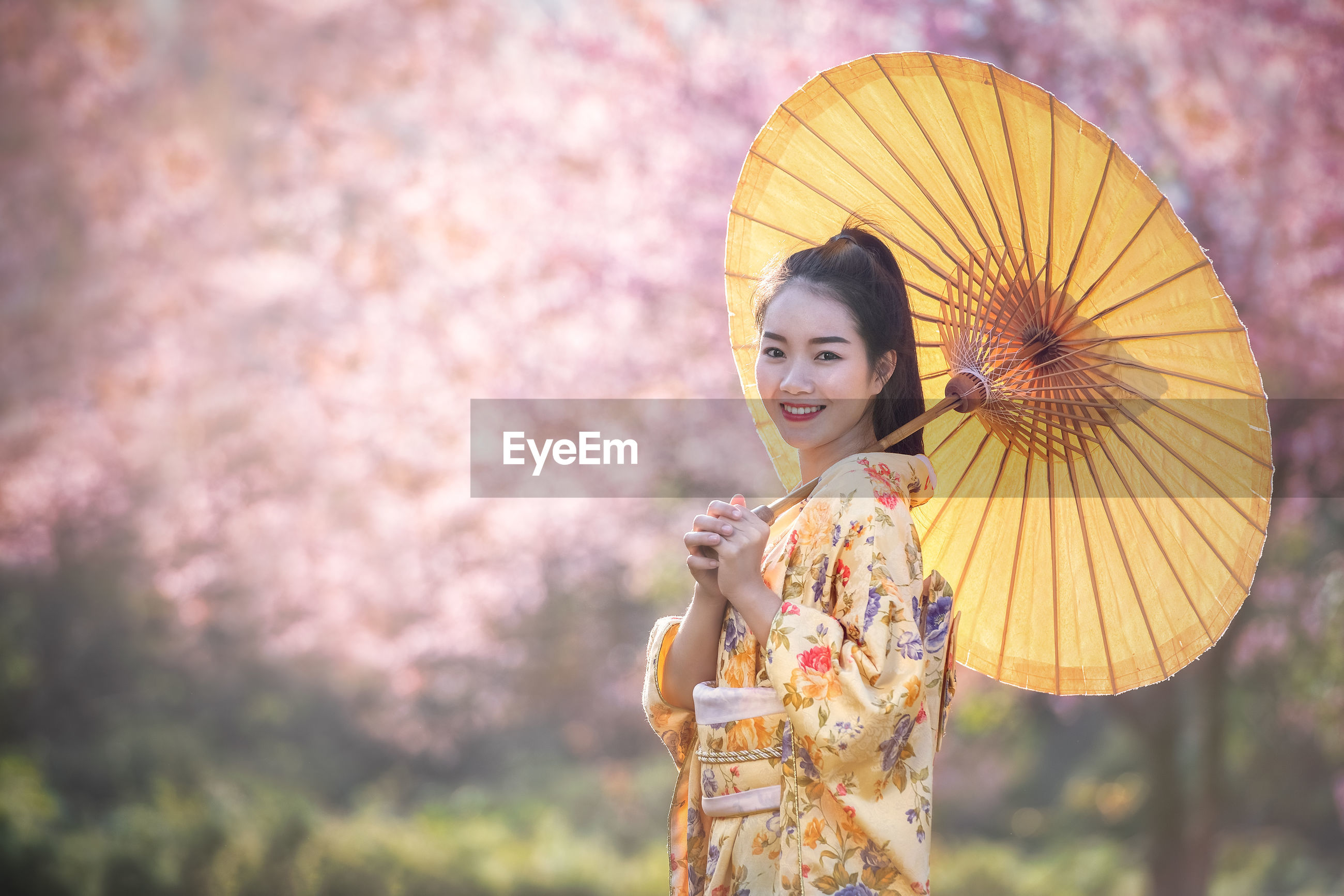 Portrait of smiling young woman with umbrella standing against cherry blossom