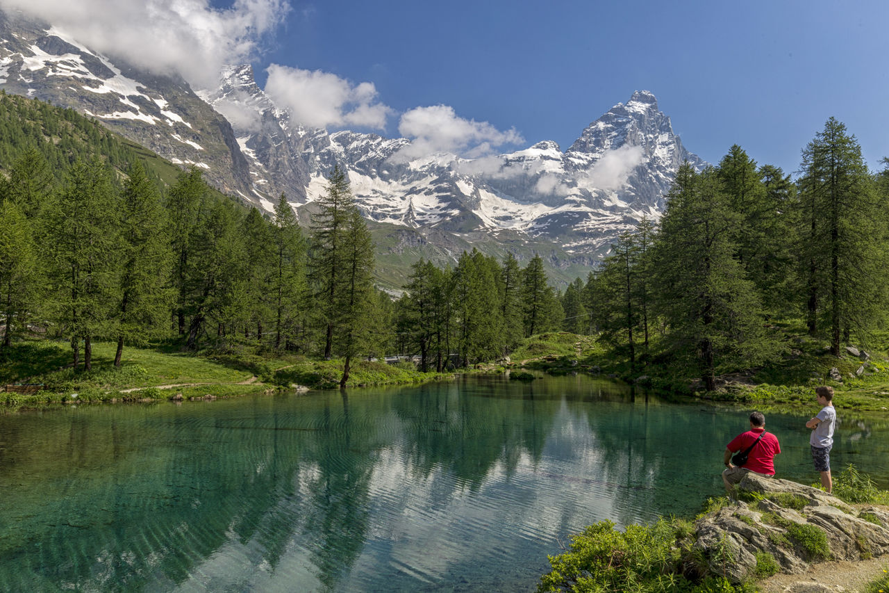 mountain, beauty in nature, scenics - nature, tree, plant, real people, water, mountain range, leisure activity, nature, lake, men, snow, cold temperature, adult, tranquil scene, tranquility, people, day, outdoors