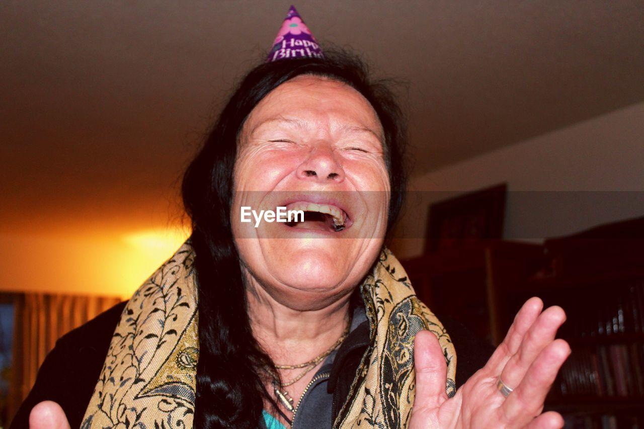 Close-up of cheerful senior woman at home