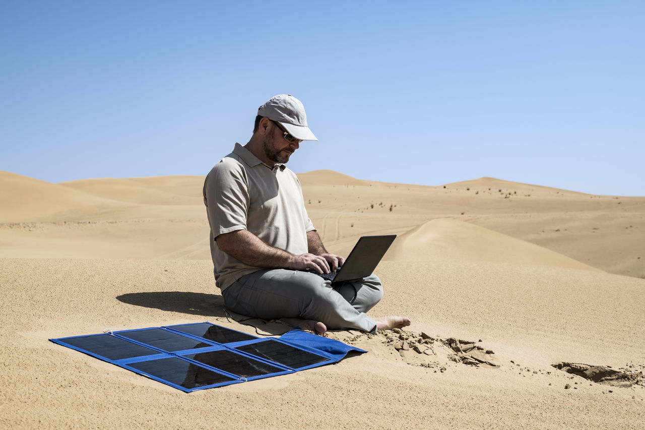 Man Using Laptop While Sitting In Desert