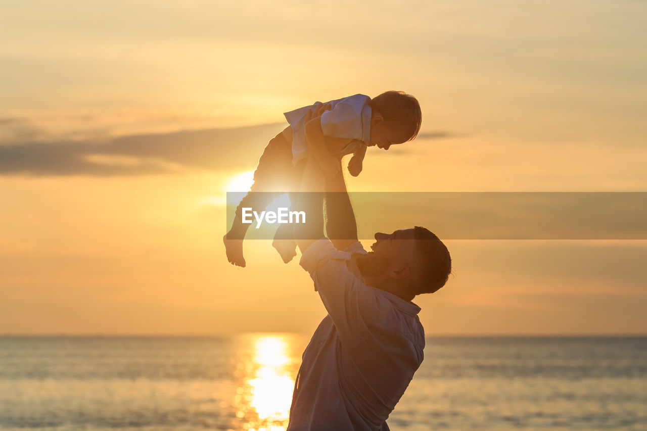 Playful father lifting son while standing by sea during sunset